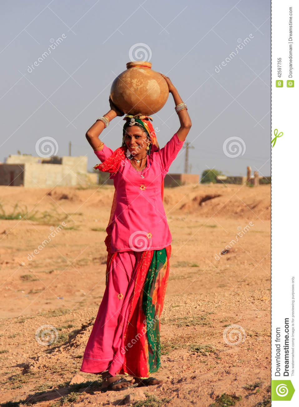 local woman carrying jar with water on her head khichan
