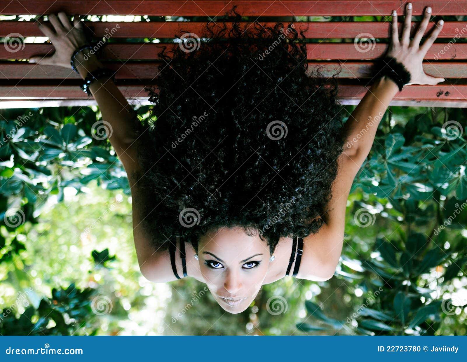 Localización africana joven de la mujer en banco en parque