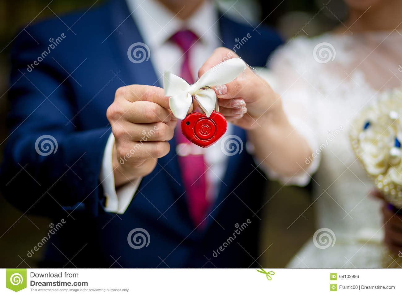 The lock in hands of the newly married couple, closeup.