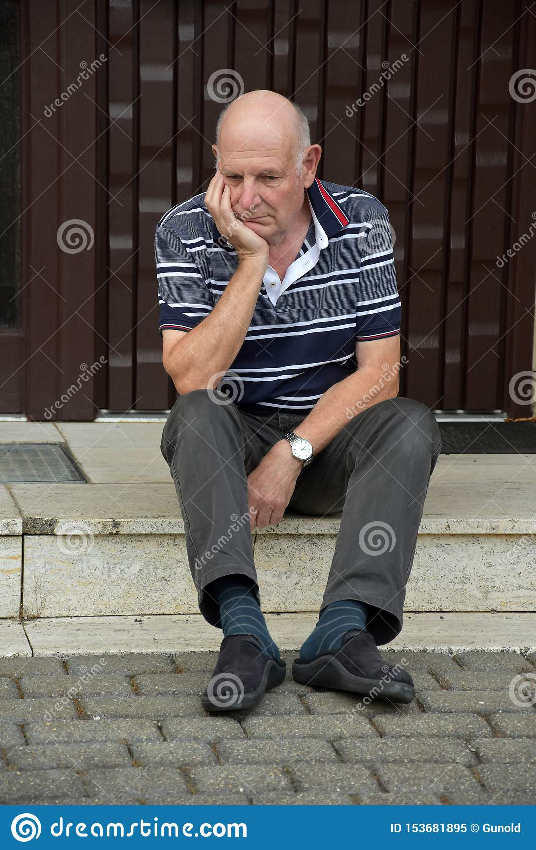 Locked out senior man sitting in front of his house
