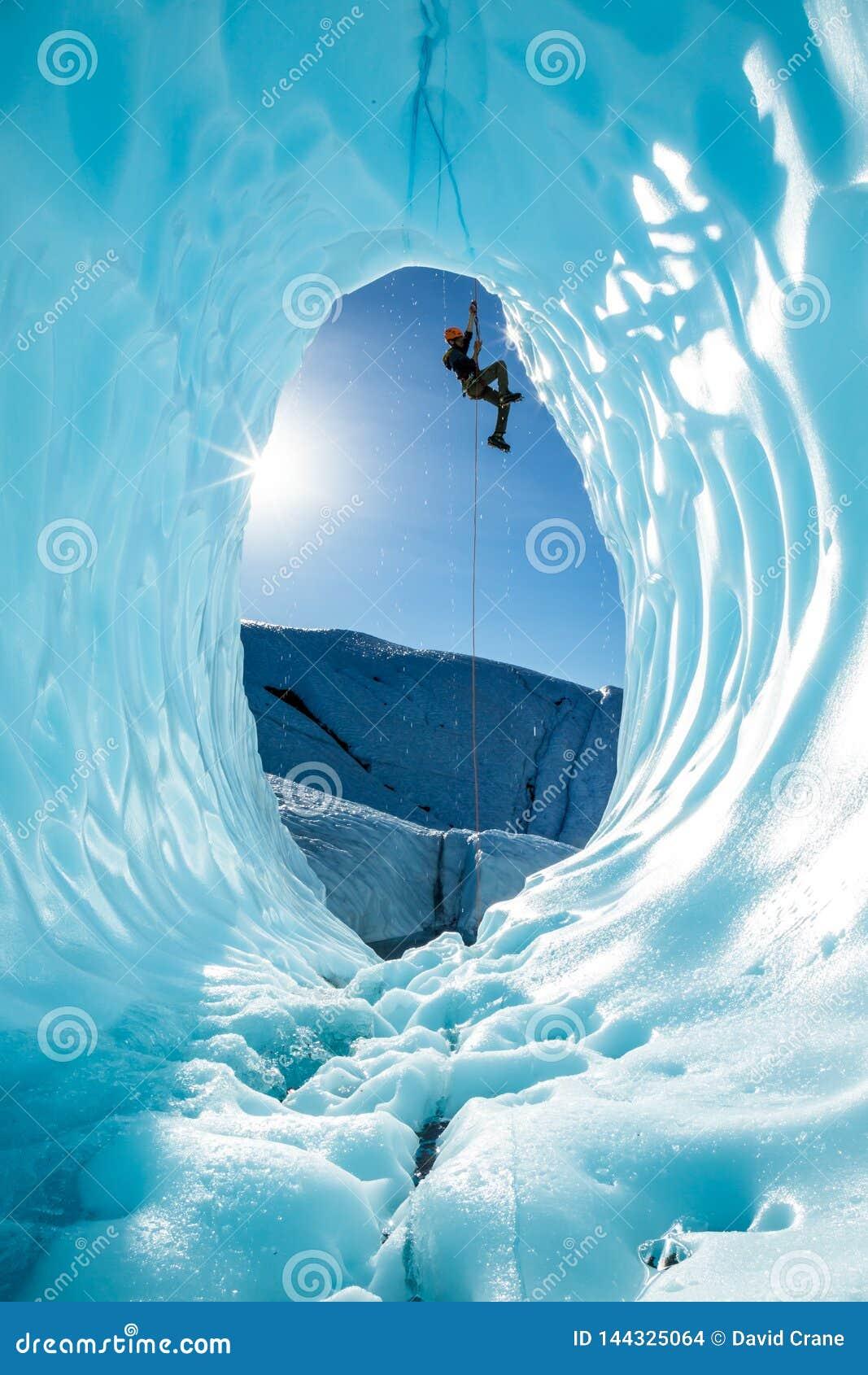 Lodowy arywista unosi się arkanę nad wejściem wielka błękitna lodowa jama na Matanuska lodowu w Alaska