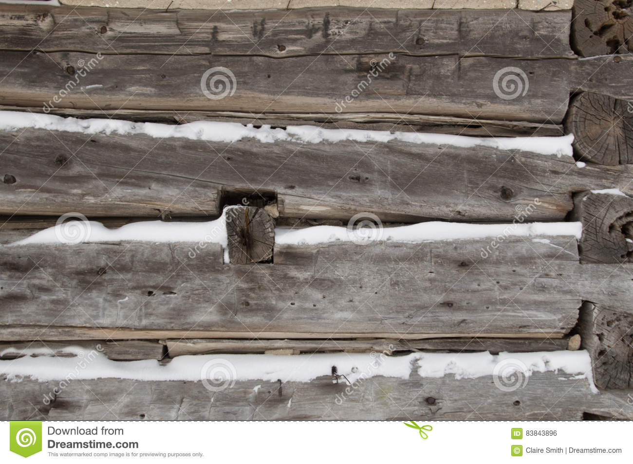 Log cabin sawn logs to corner closeup with snow in between