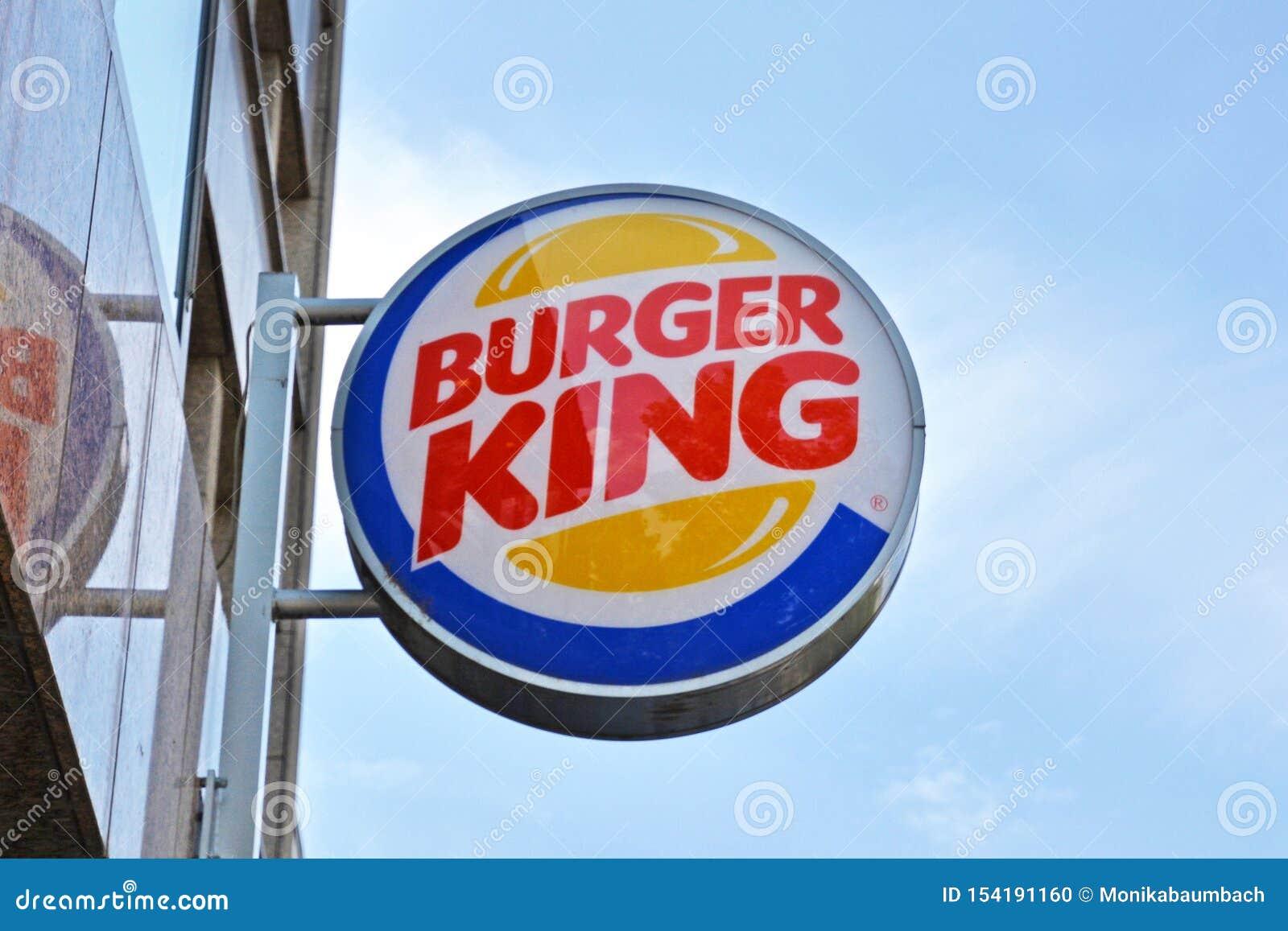 Logo av hamburgaresnabbmatkedjan 'Burger King 'som hänger utanför främst av blå himmel