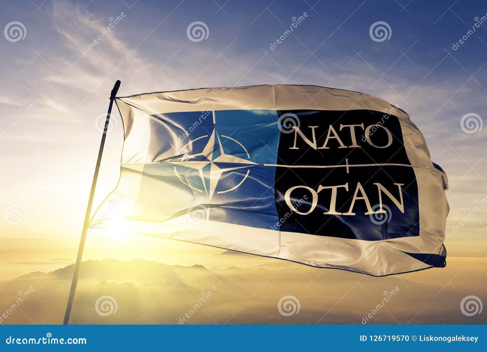 Logo för NATO OTAN för organisation för fördrag för norrAtlanten tyg för flaggatextiltorkduk som vinkar på den bästa soluppgångmi