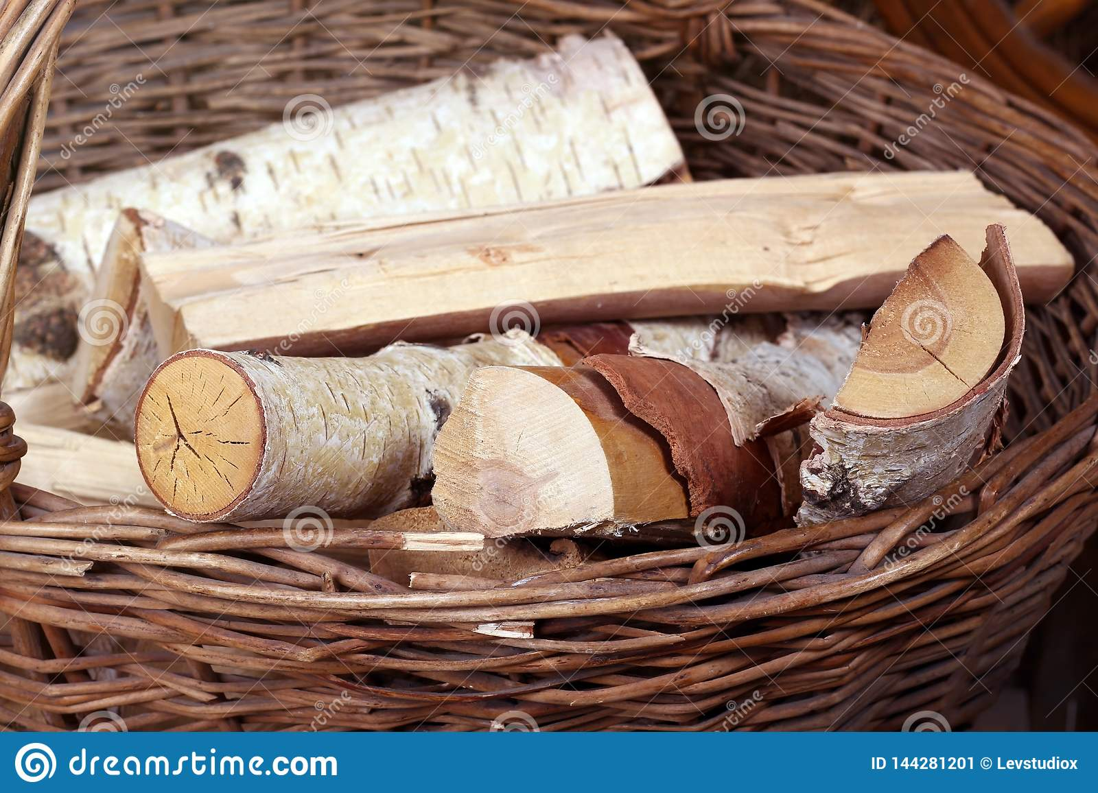 Logs lie in a wicker basket with a handle on the background of haystacks