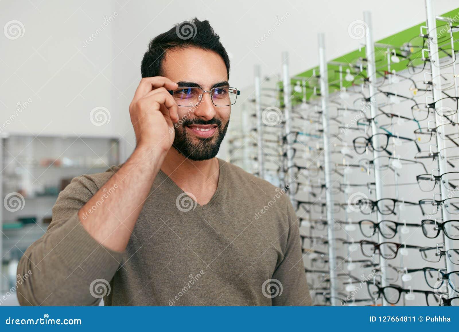 Loja dos vidros Homem que tenta em monóculos na loja do sistema ótico