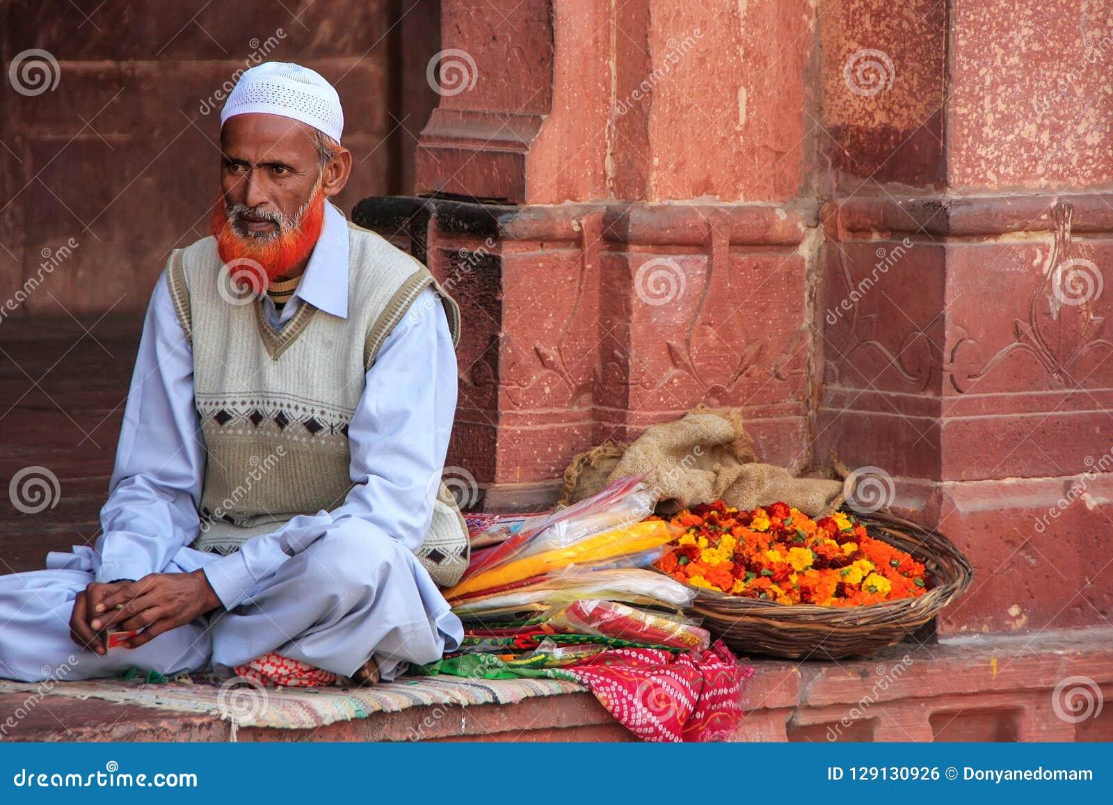 Lokaler Mann, der Blumen im Hof von Jama Masjid im Fett verkauft