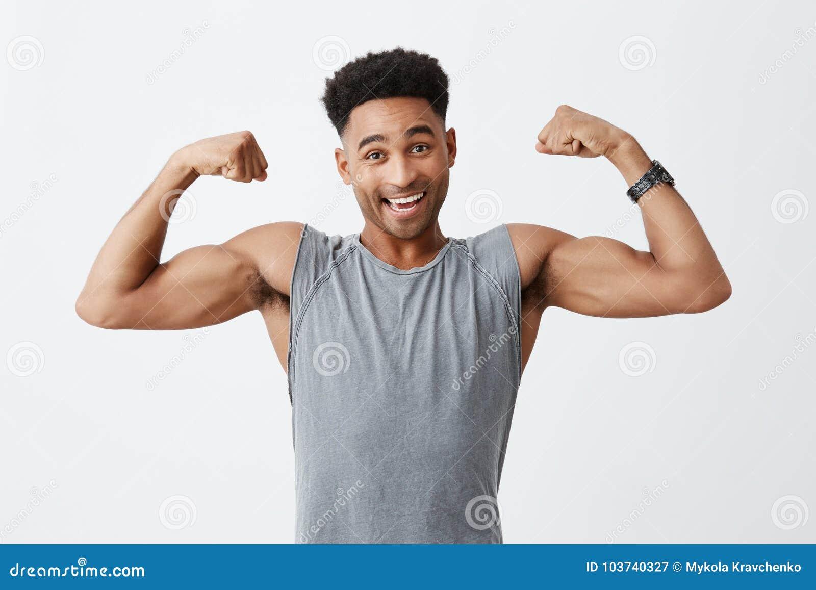 Lokalisiertes Porträt des jungen netten attraktiven athletischen dunkelhäutigen Mannes mit Afrofrisur im sportlichen grauen Hemd