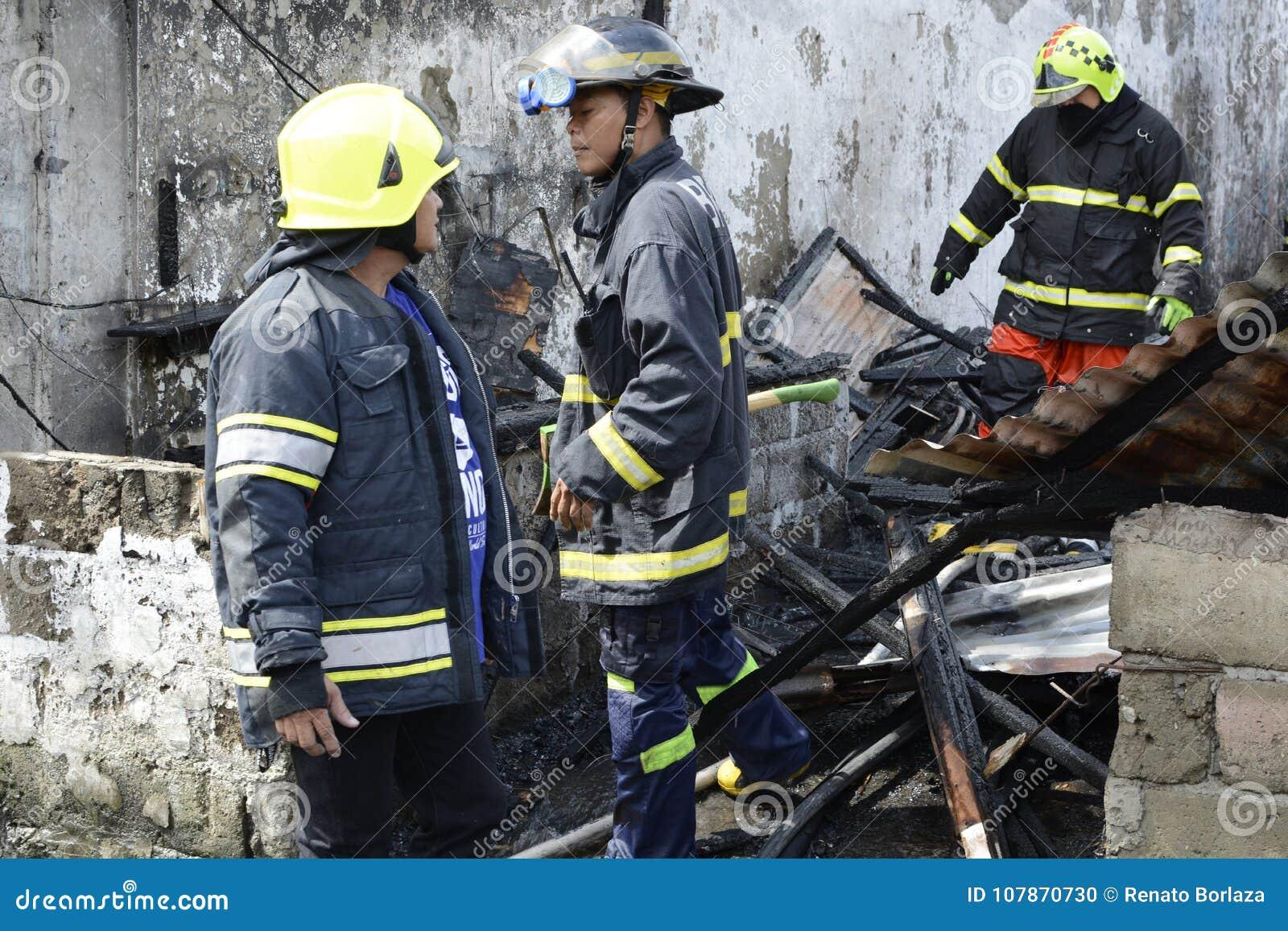 Lokalna palacz pomoc gasi ogienia podczas domu ogienia który patroszył wewnętrznych szanta domy