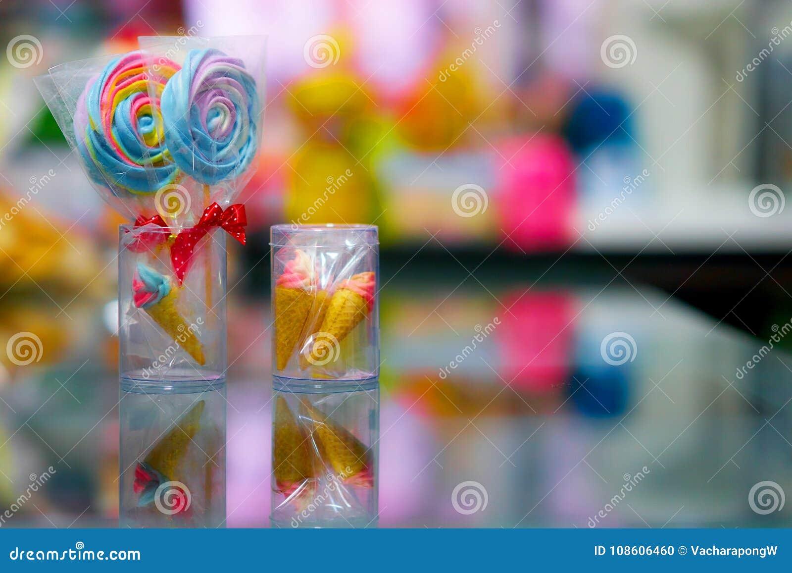 Lolipop colorido e mini cone na caixa plástica com reflexão