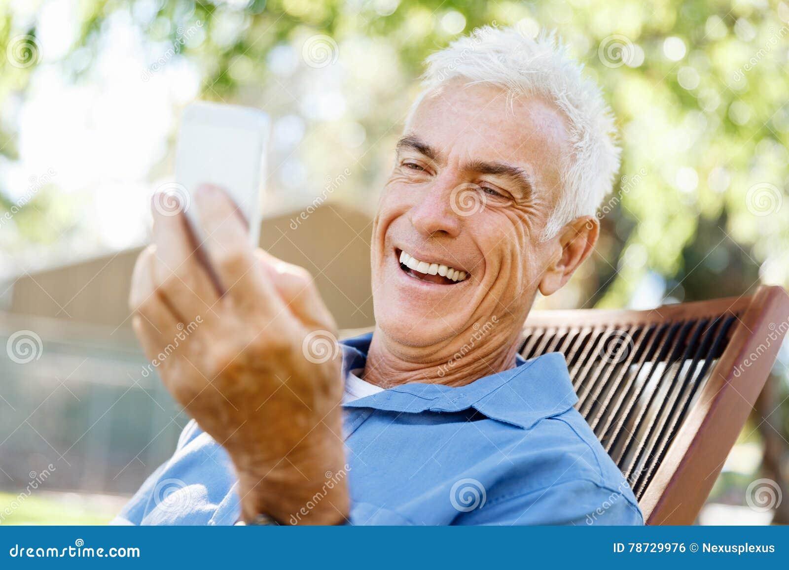 LoMature man som använder utomhus mobiltelefonen