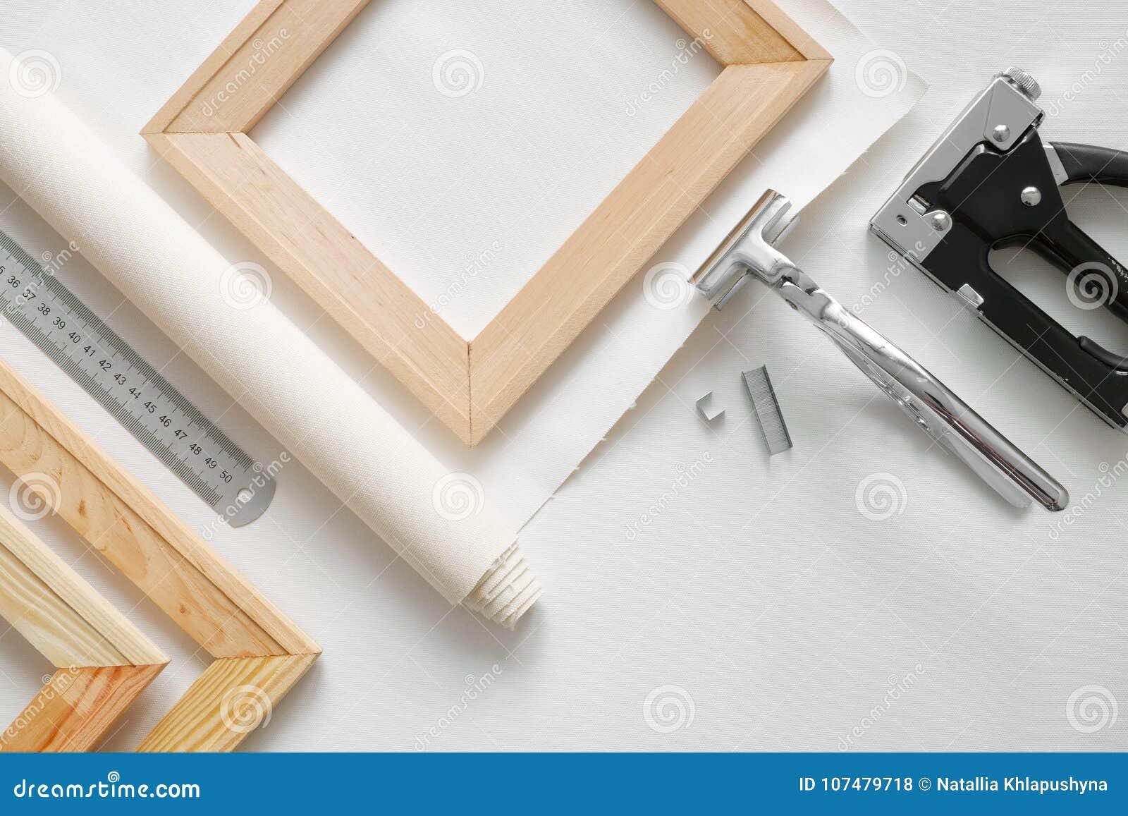 A lona do artista no rolo, as barras de madeira da maca, as empilhadeiras da maca de lona e o grampo atiram