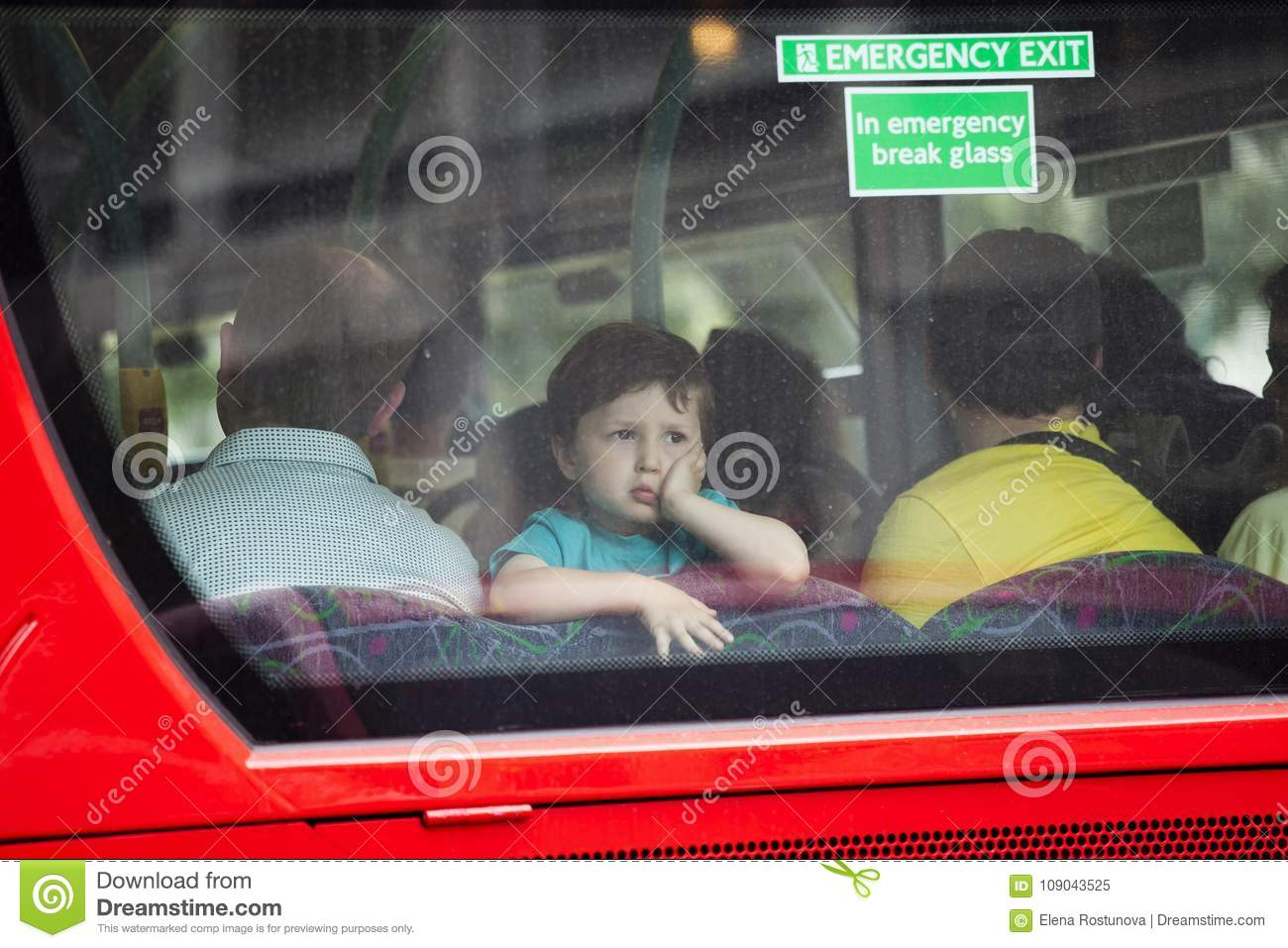 A boy of four looks at the rear window of a bus