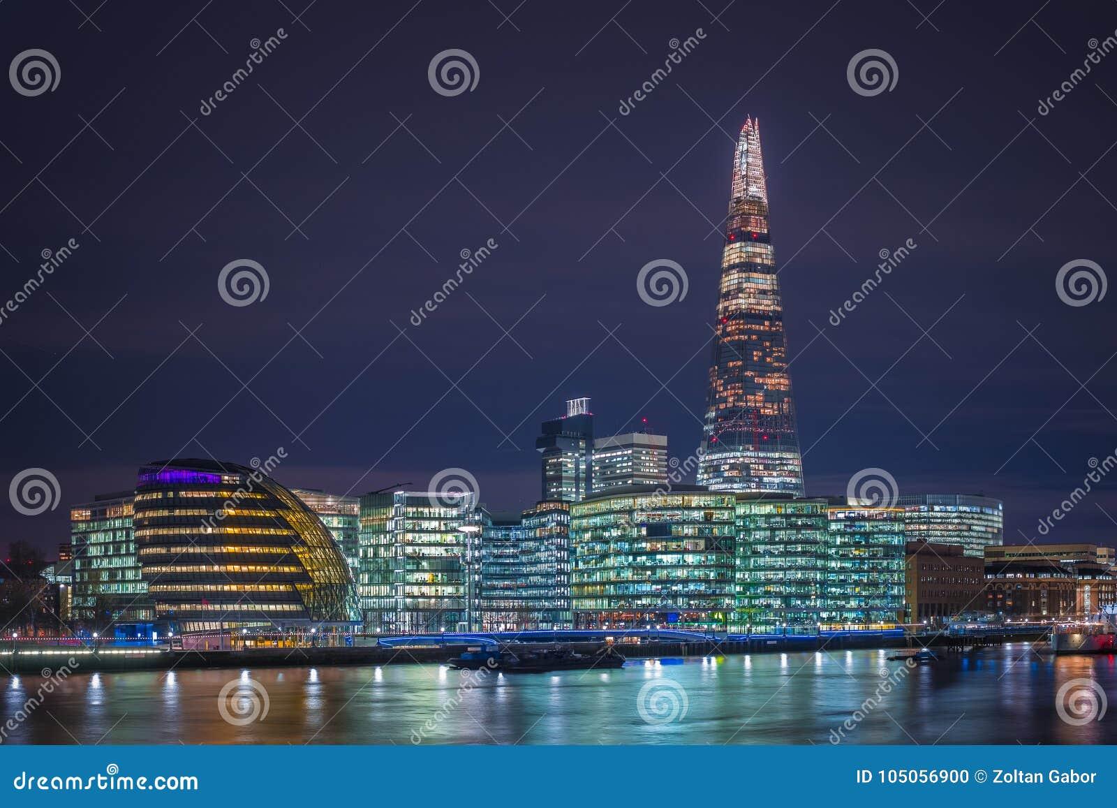 London, England - stadshus av London och kontor med den berömda skärvaskyskrapan vid natt