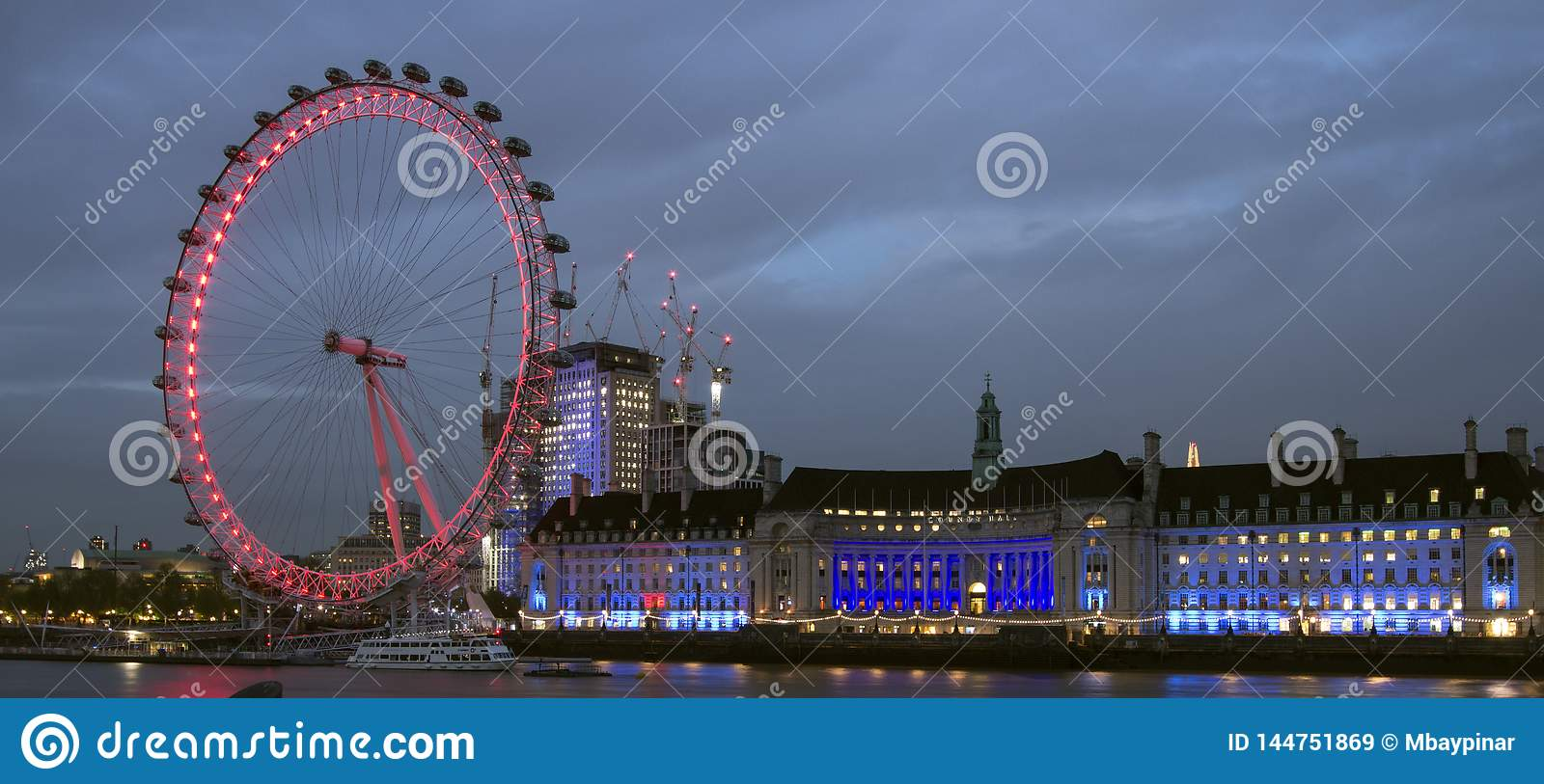London Eye and County Hall by night, pink and blue.