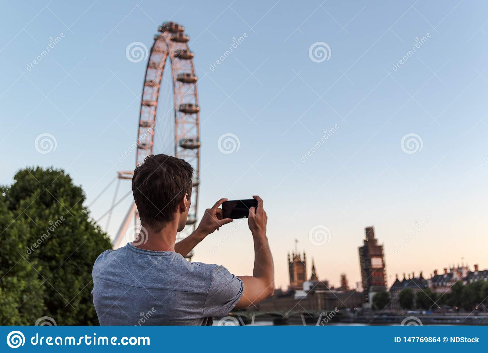 One young man taking a picture of the big ben during renovation