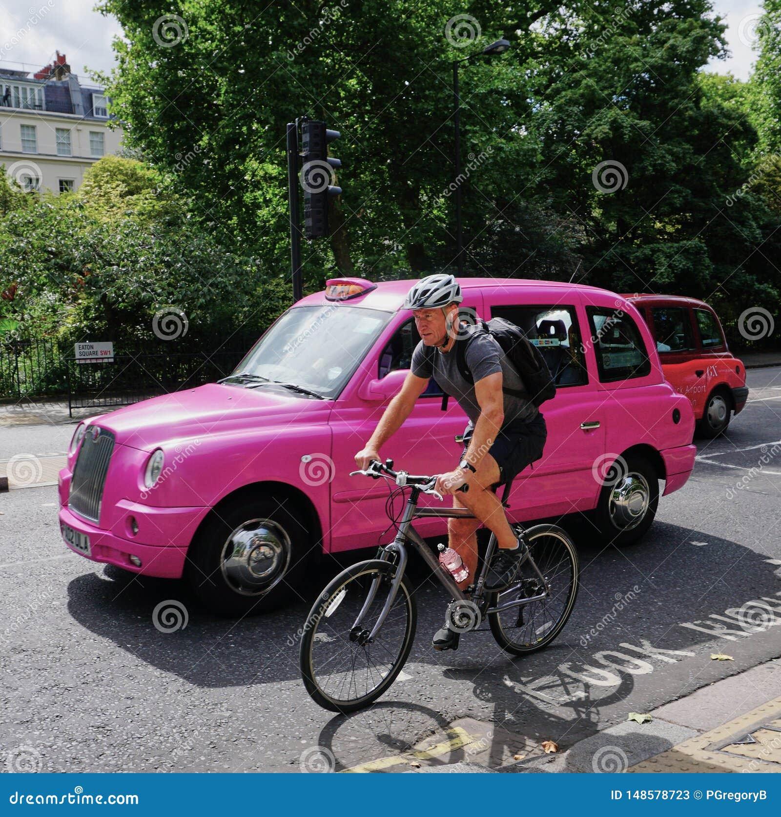 London gataplats med den ovanliga rosa klassiska taxin och cyklisten