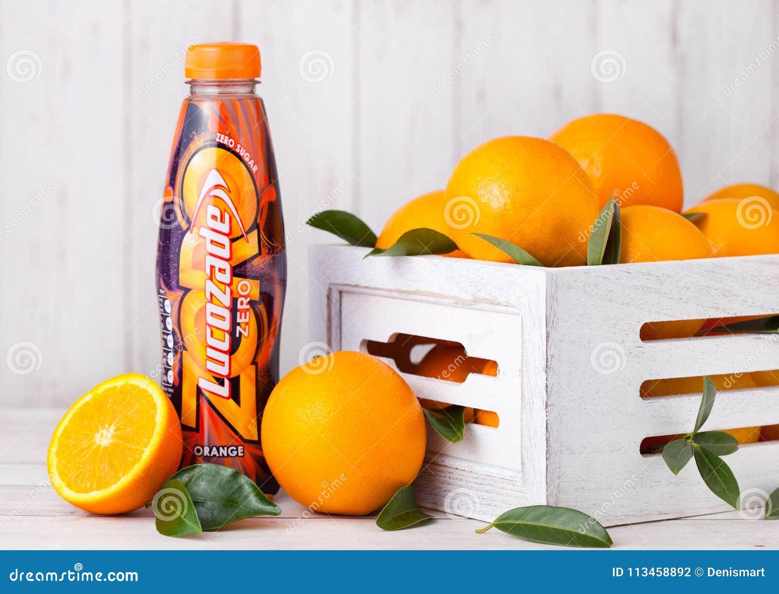 LONDON, GROSSBRITANNIEN - 31. MÄRZ 2018: Plastikflasche des alkoholfreien Getränkes Lucozade-Orange null mit frischen rohen Orang