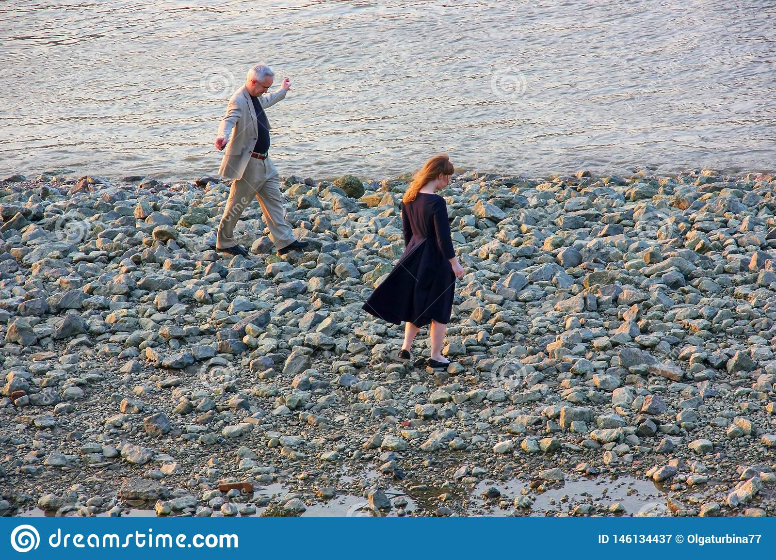 An elderly man  with his granddaughter, a student are joyful walking on the rocky bank of the Thames in the evening