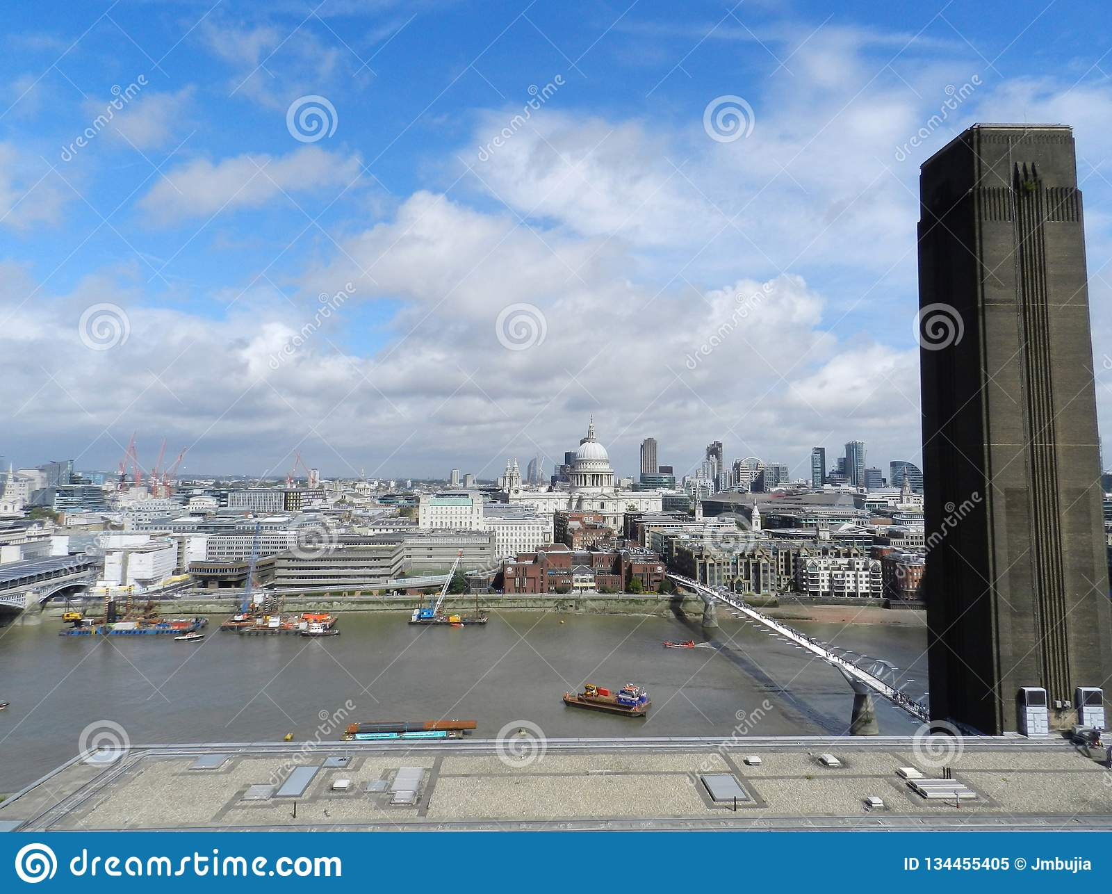 London, United Kingdom. Millenium Bridge, St. Paul's Cathedral and the City from Tate Modern viewpoint.
