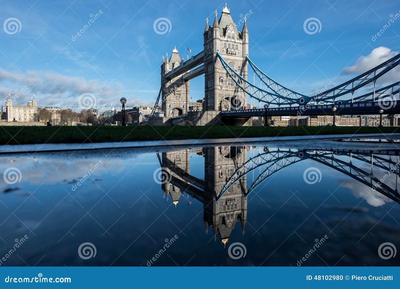 London - tornbro reflekterad i en regnpöl