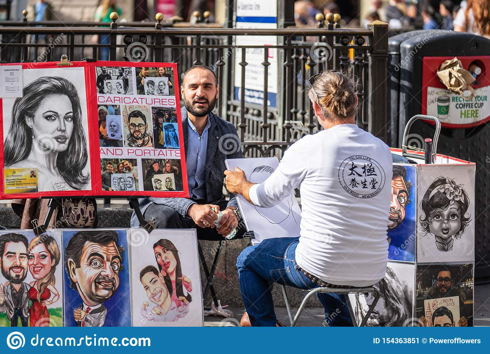 London, UK, July 14, 2019. The street artist is sketching models portrait. Caricaturist drawing people with different styles