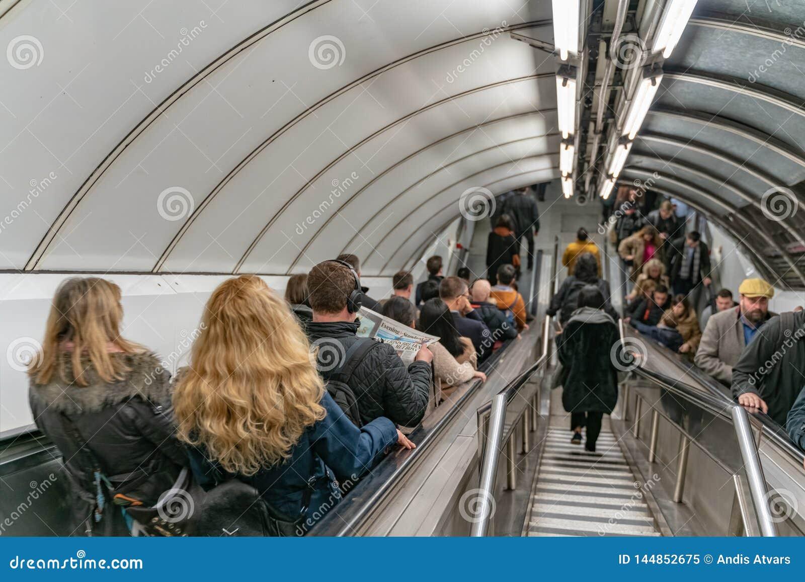 London UK - 05, mars 2019: Bankstationen i den London tunnelbanan, folk anv?nder rulltrappan p? rusningstiden