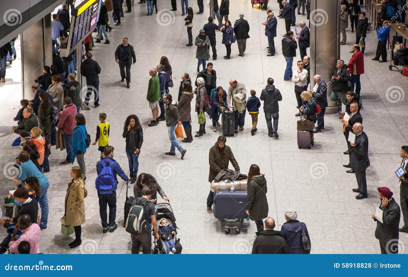LONDON UK - MARS 28, 2015: Väntande på ankomster för folk i Heathrow flygplatsterminal 5
