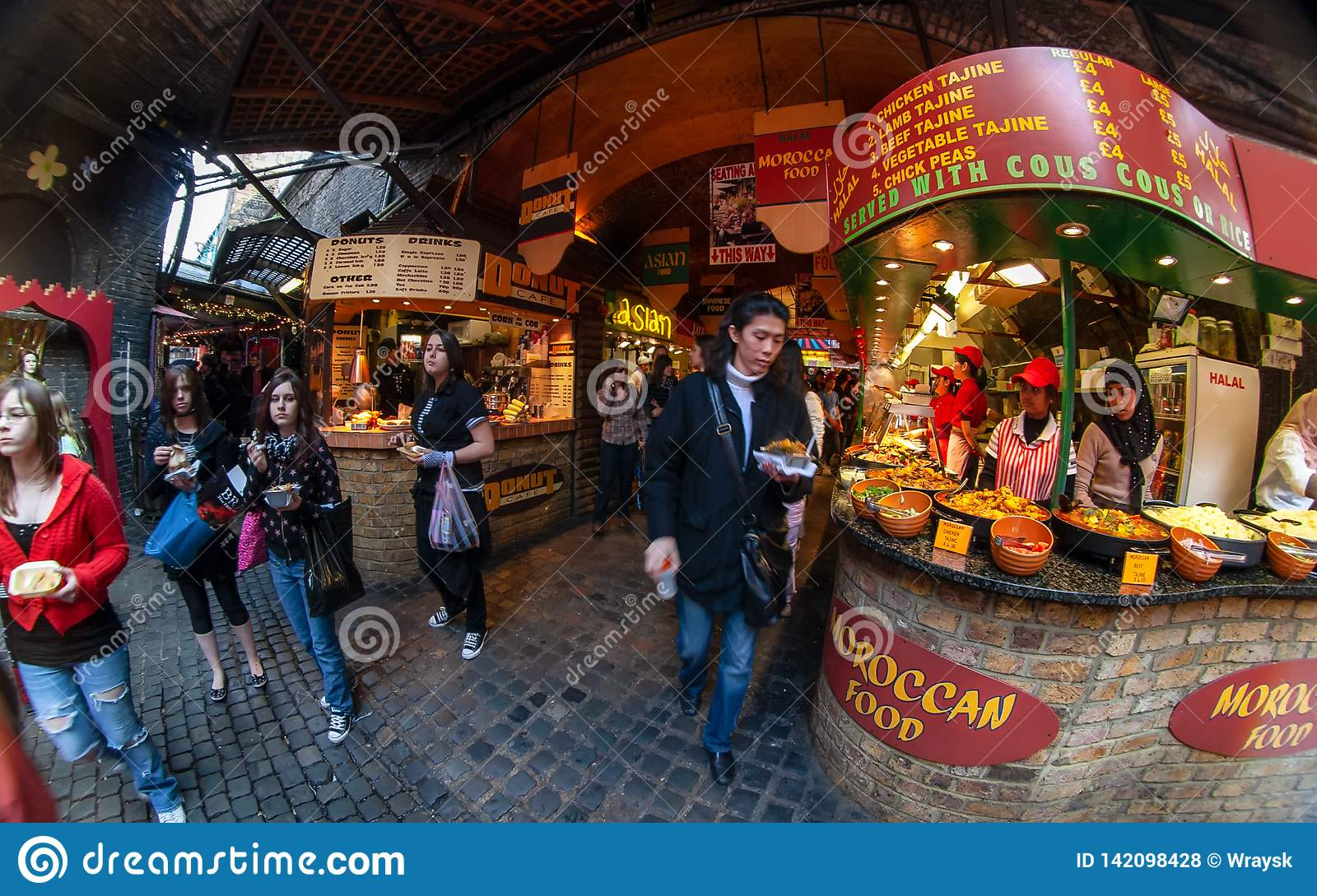 London, United Kingdom - March 31, 2007: Unknown shoppers eating street food while walking at Camden Lock, famous market