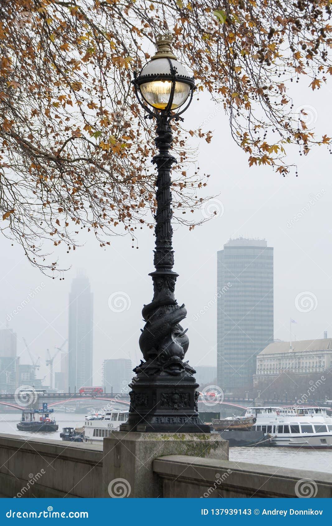 LONDON, VEREINIGTES KÖNIGREICH - 23. NOVEMBER 2018: Nebelhaft Ansicht der Themse und der alten Straßenbeleuchtung