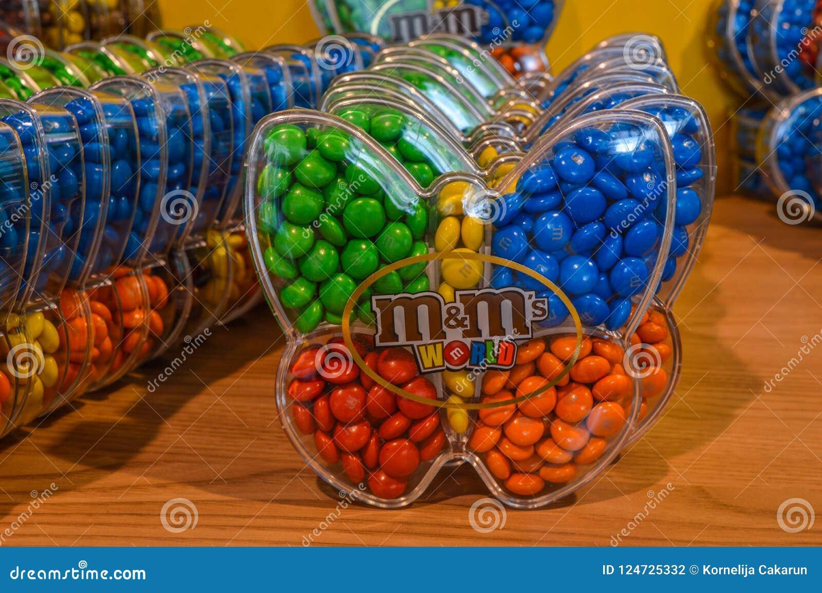 Londra, Regno Unito - 7 agosto 2018: Le caramelle di cioccolato variopinte del ` s di M&M in farfalla hanno modellato i contenito