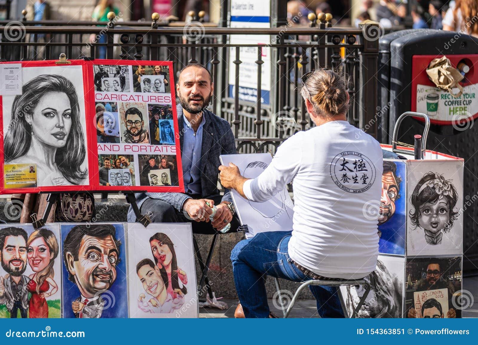 Londra, Regno Unito, il 14 luglio 2019 L artista della via sta schizzando il ritratto dei modelli Gente di disegno del caricaturi