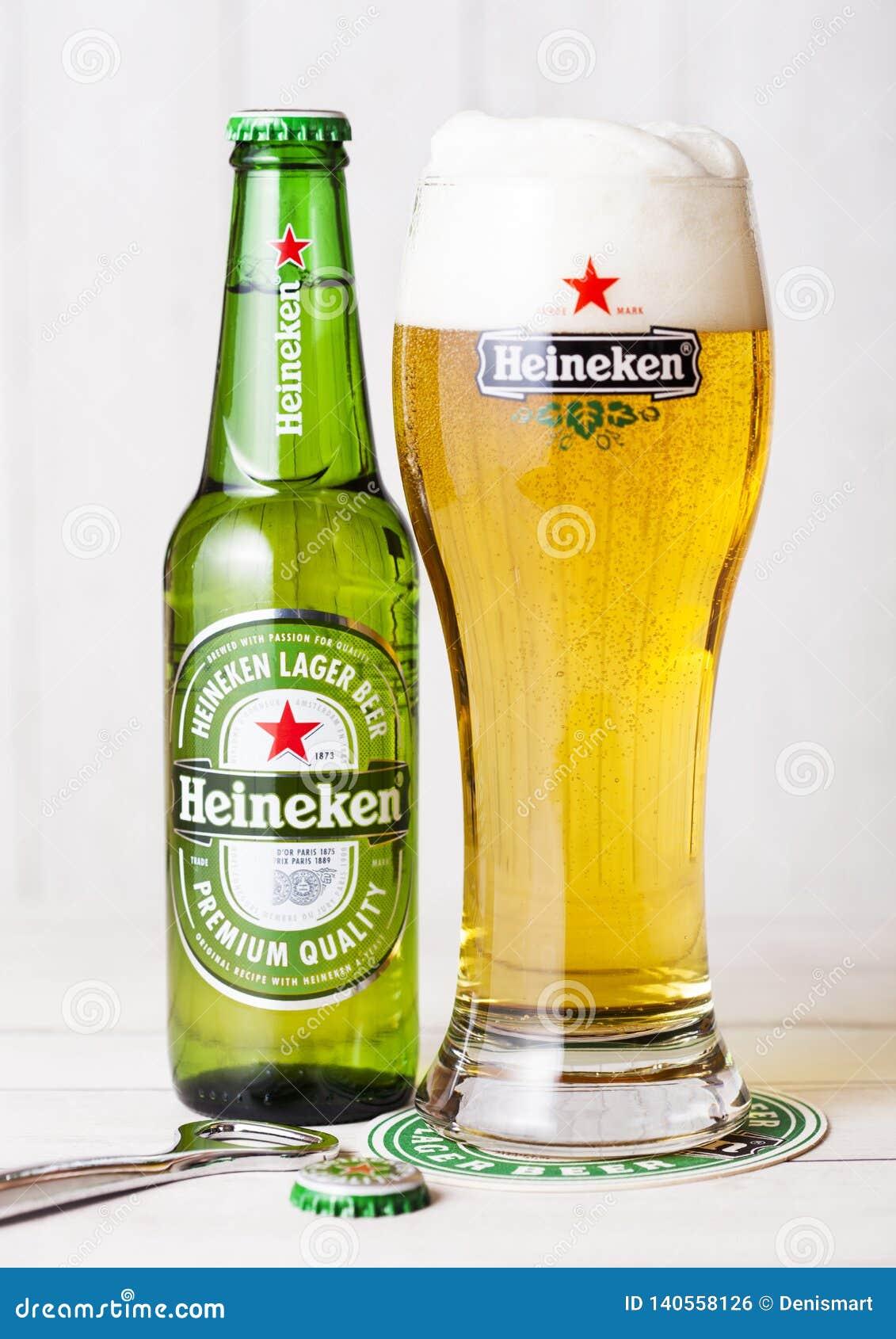 LONDRES, REINO UNIDO - 27 DE ABRIL DE 2018: Botella de Heineken Lager Beer en fondo de madera con el vidrio original