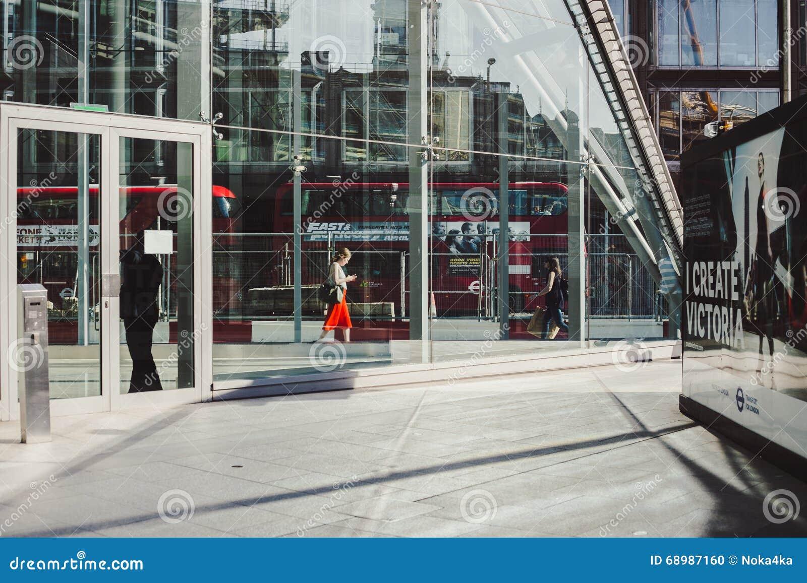 LONDRES, Reino Unido - 14 de abril de 2015: mujer de negocios joven que camina a lo largo del camino con tráfico y de los autobus