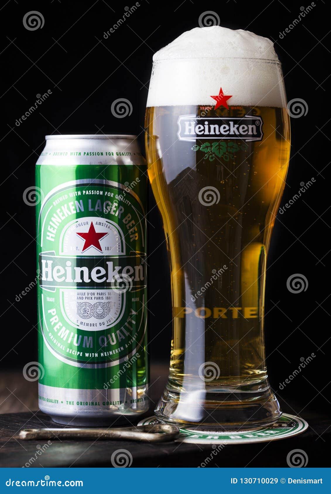 LONDRES, REINO UNIDO - 27 DE ABRIL DE 2018: Poder de aluminio y vidrio original de Heineken Lager Beer en fondo de madera oscuro