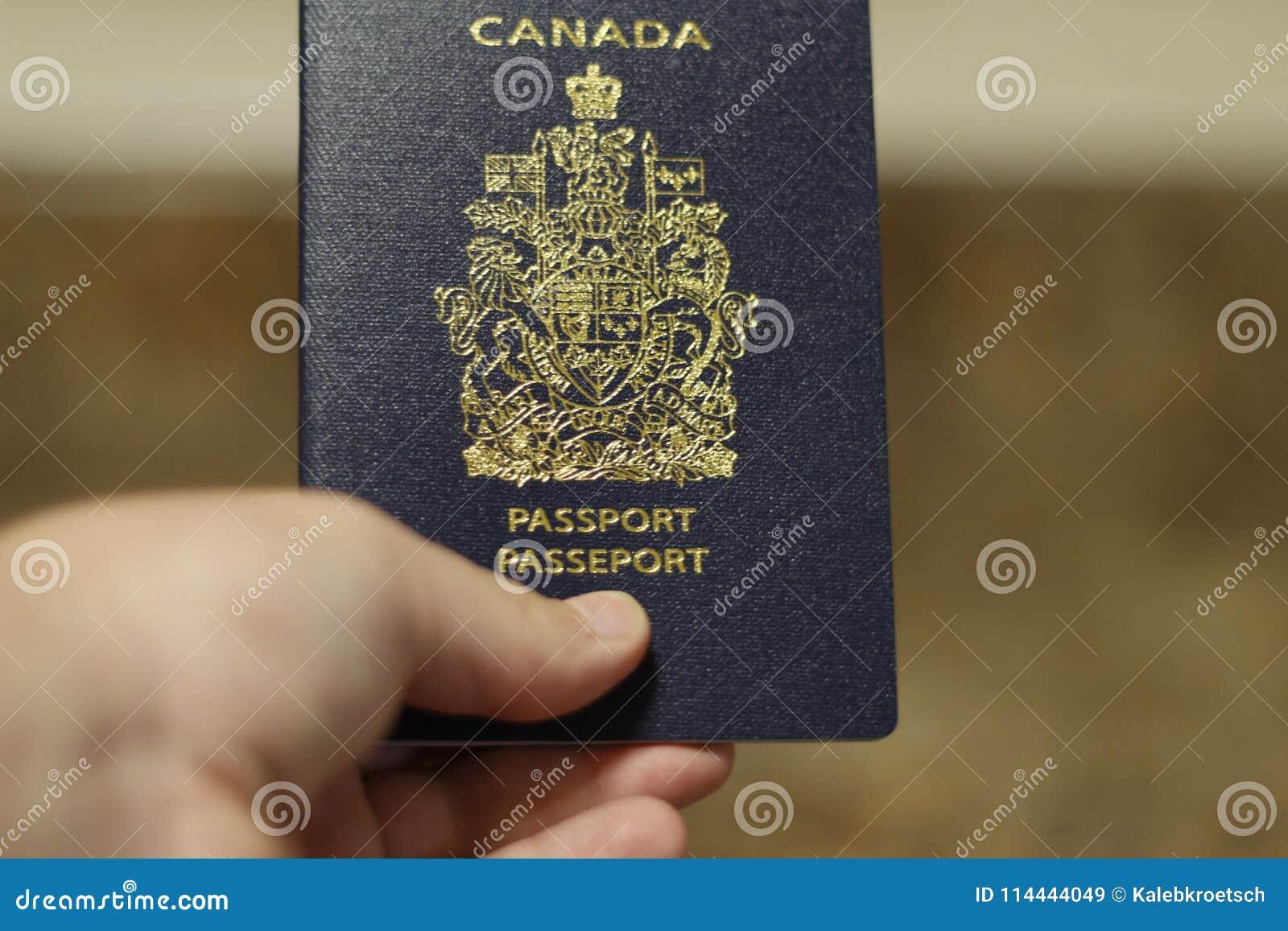 Londyński Ontario Kanada, Kwiecień 14 2018 -: Mężczyzna trzyma Kanadyjskiego paszport odizolowywający Kanadyjski paszport jest je