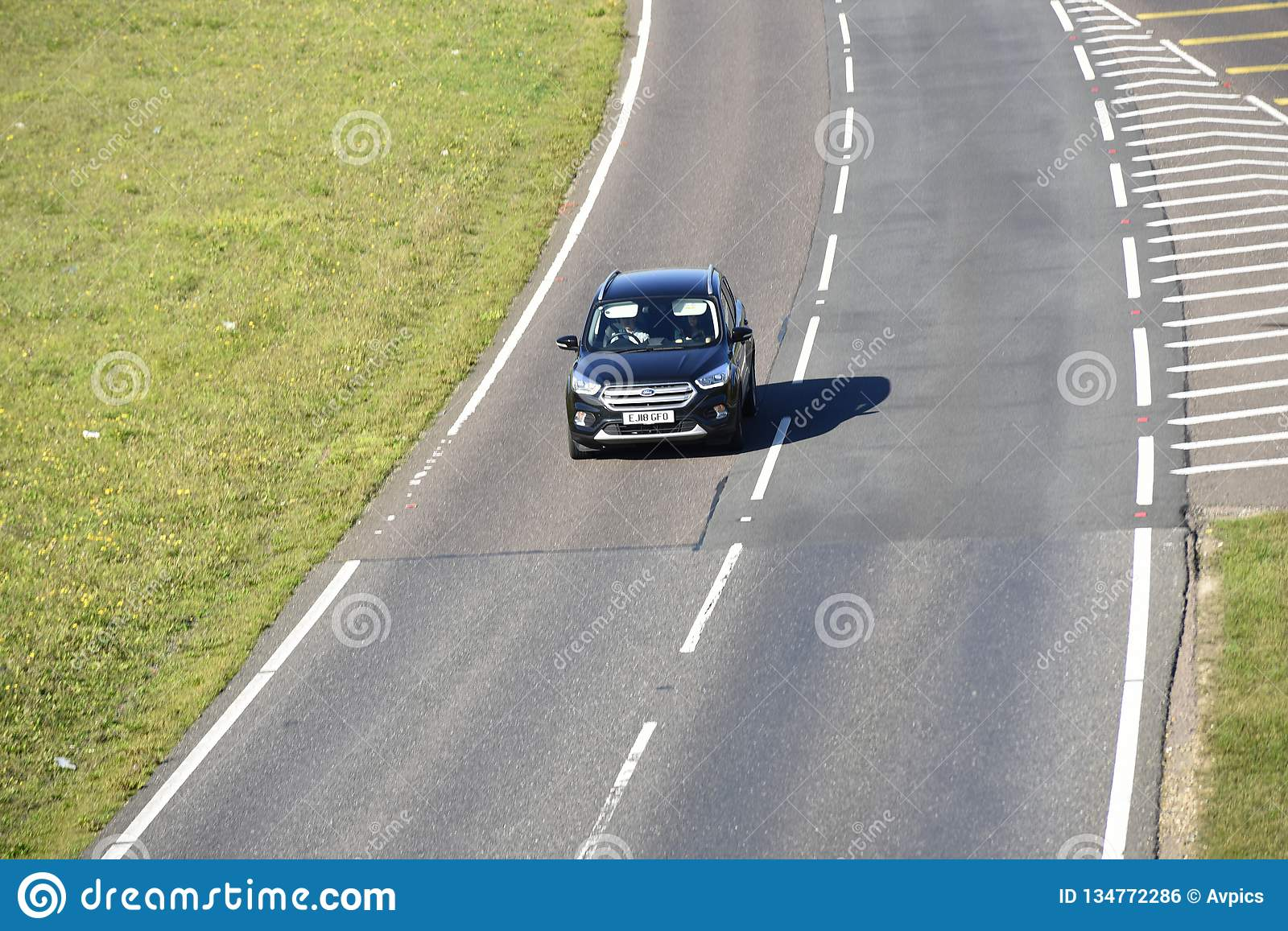 Lone car driving on a stretch of duel carriageway