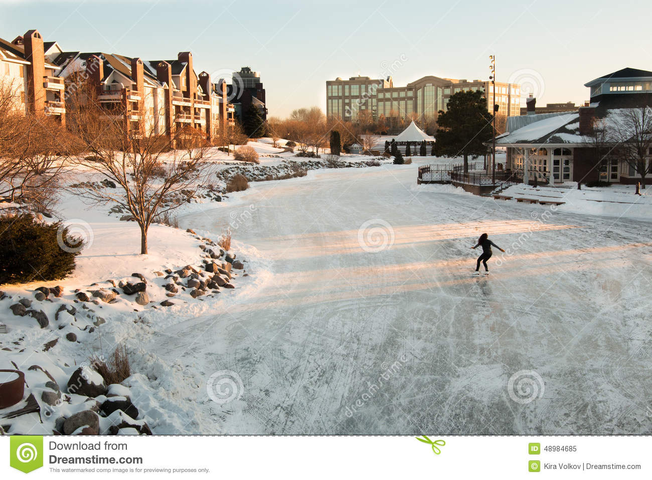 Lone figure skater on a frozen lake at early evening