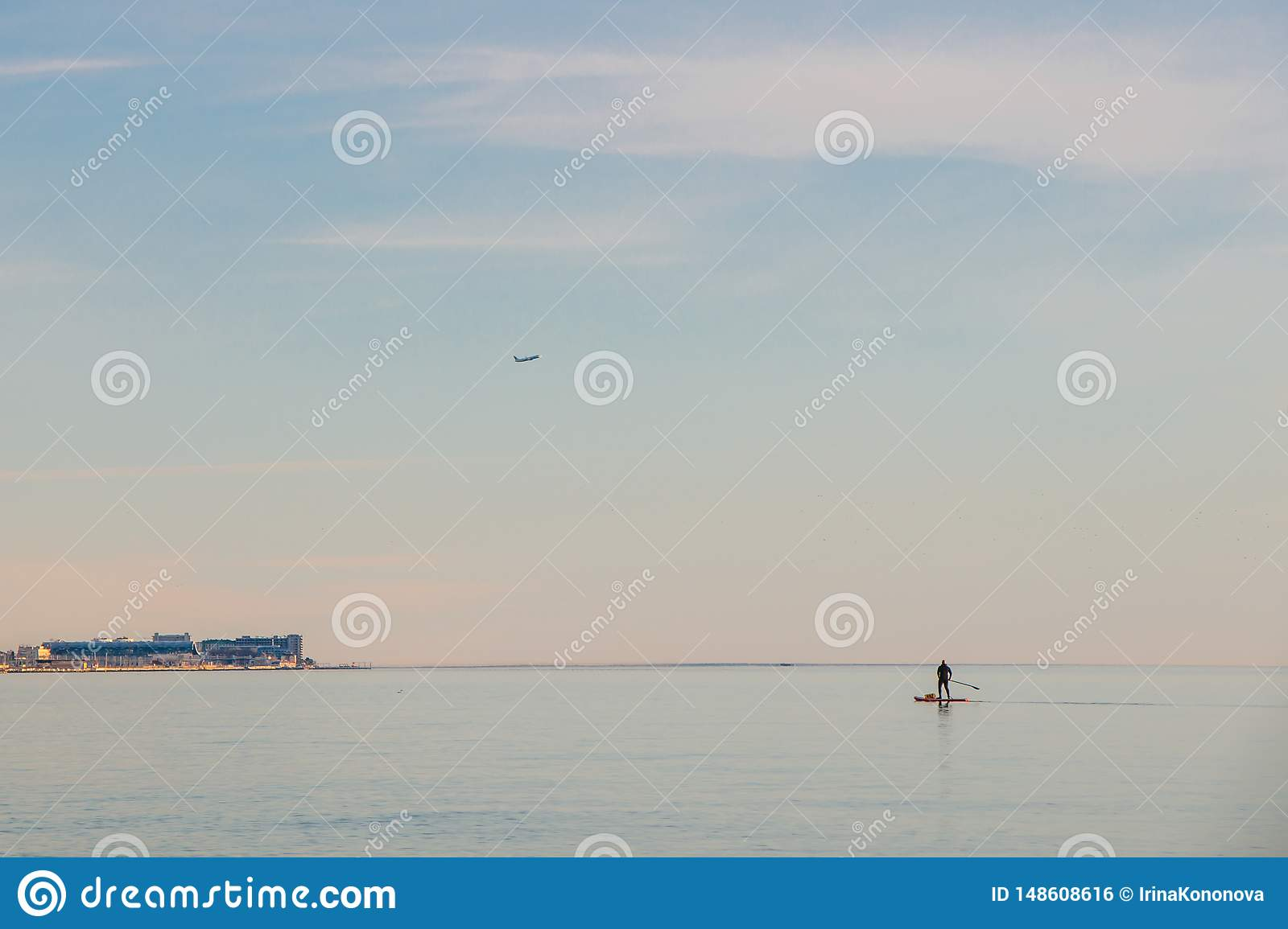 A lone man with a bag moving across the sea on a surfboard with an oar. Minimalism