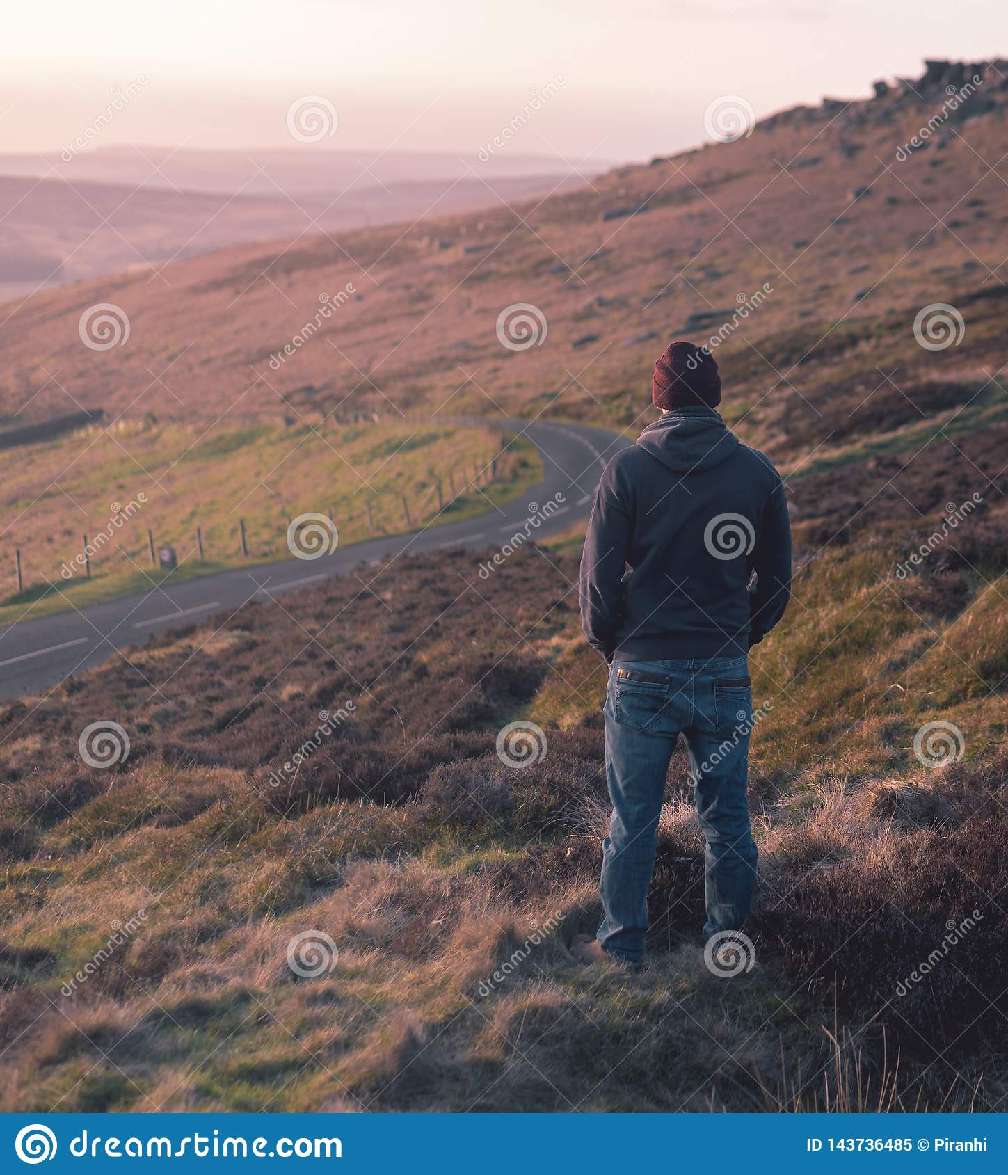Lone man stares out over grassland during sunset