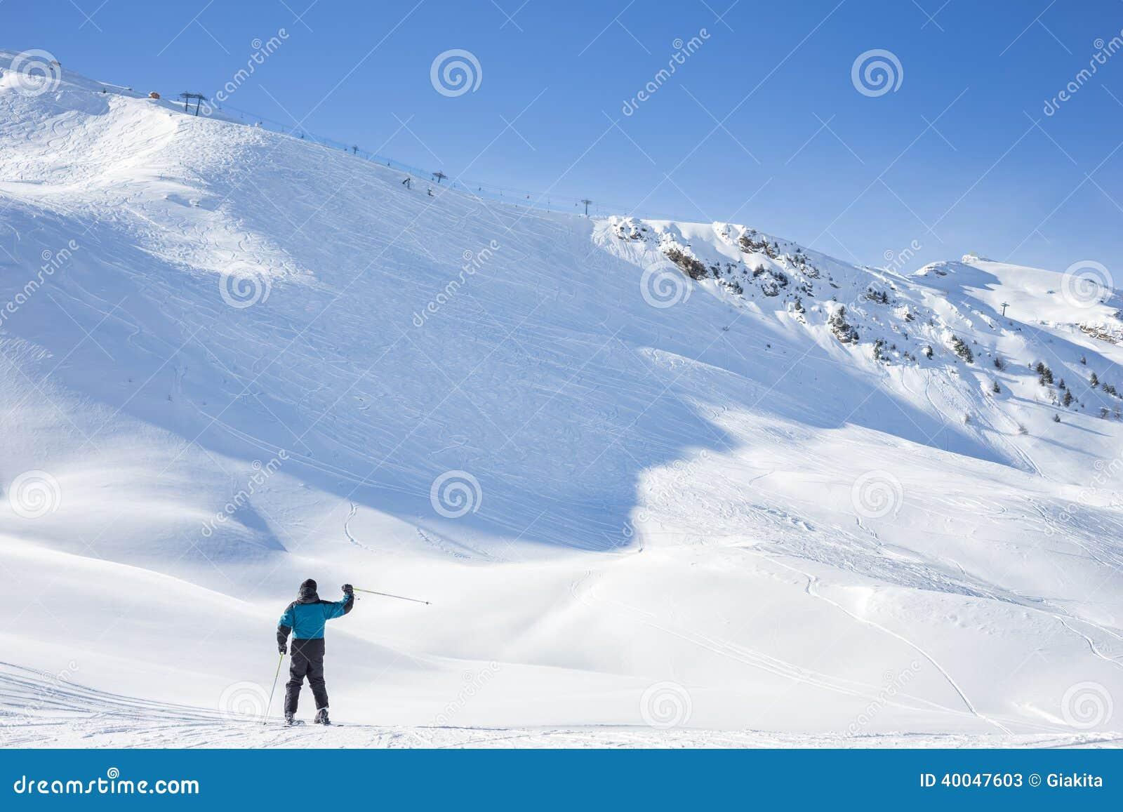 Lone skier waving on a snowy mountain peak