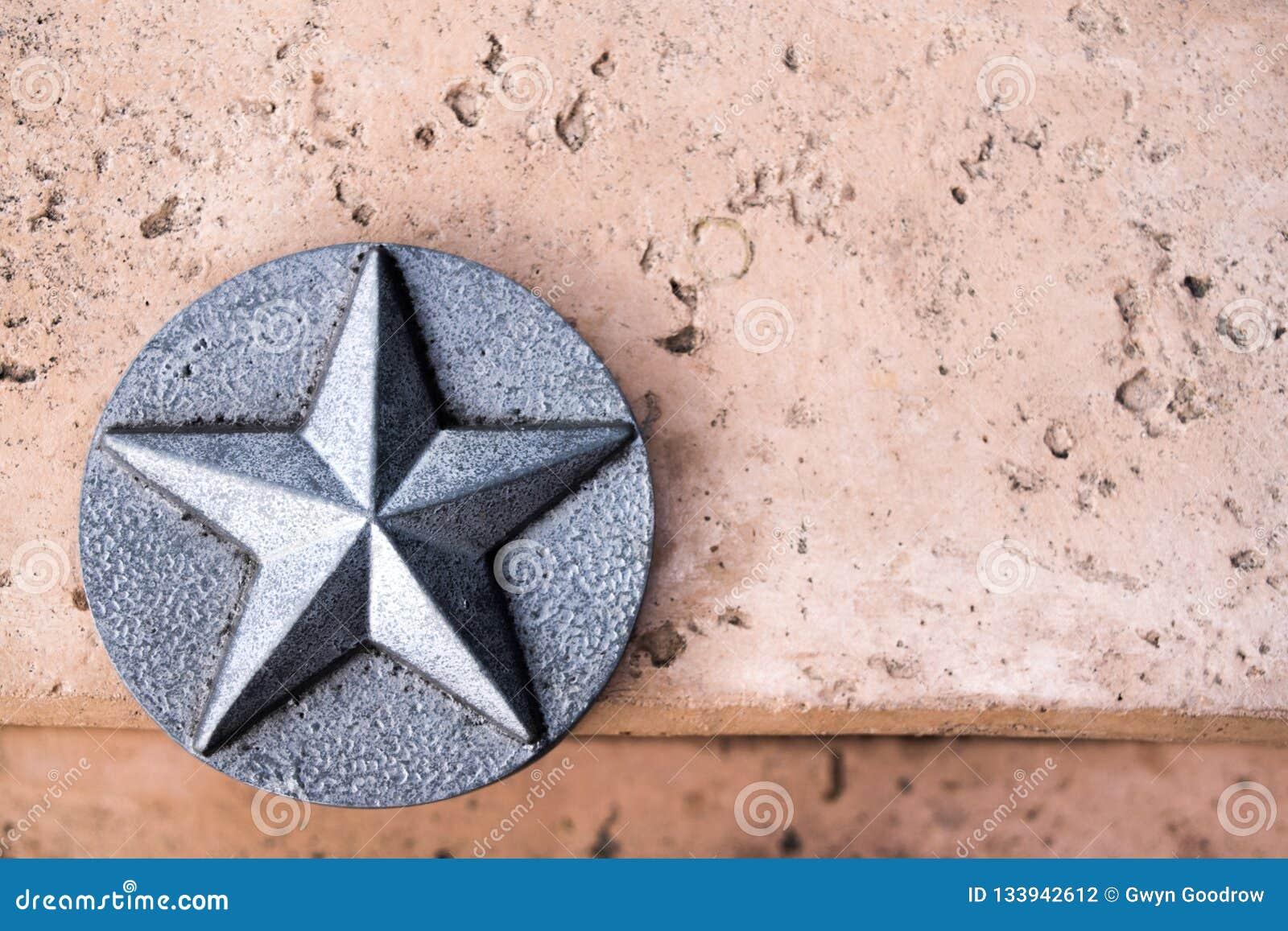 Lone Star do emblema de Texas Silver no concreto cor-de-rosa