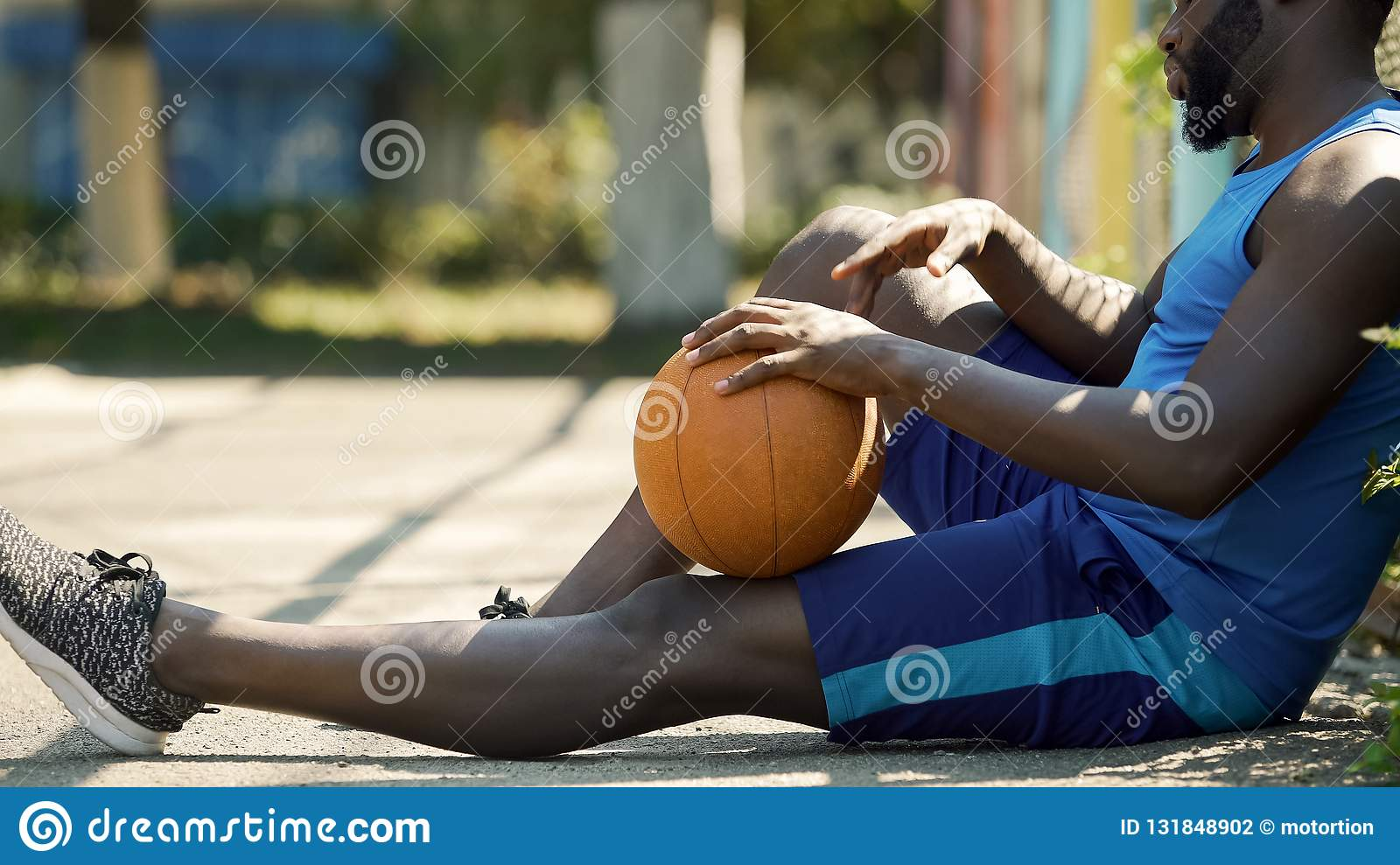Lonely Afro-American basketball player sitting on ground with ball, sadness
