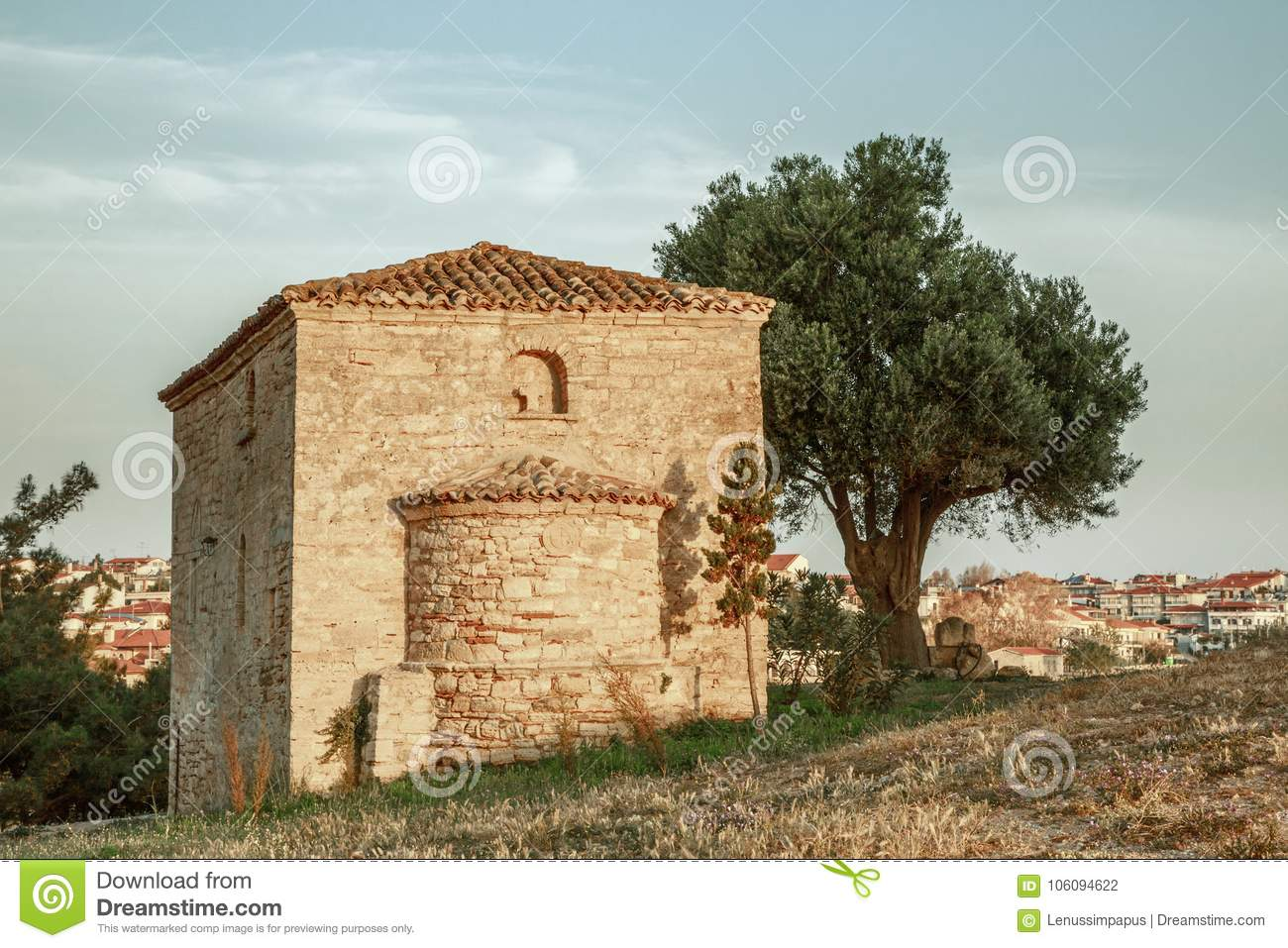 a lonely ancient chapel under a tree on the hill of the sea coast in a coastal Greek village at dawn of the day