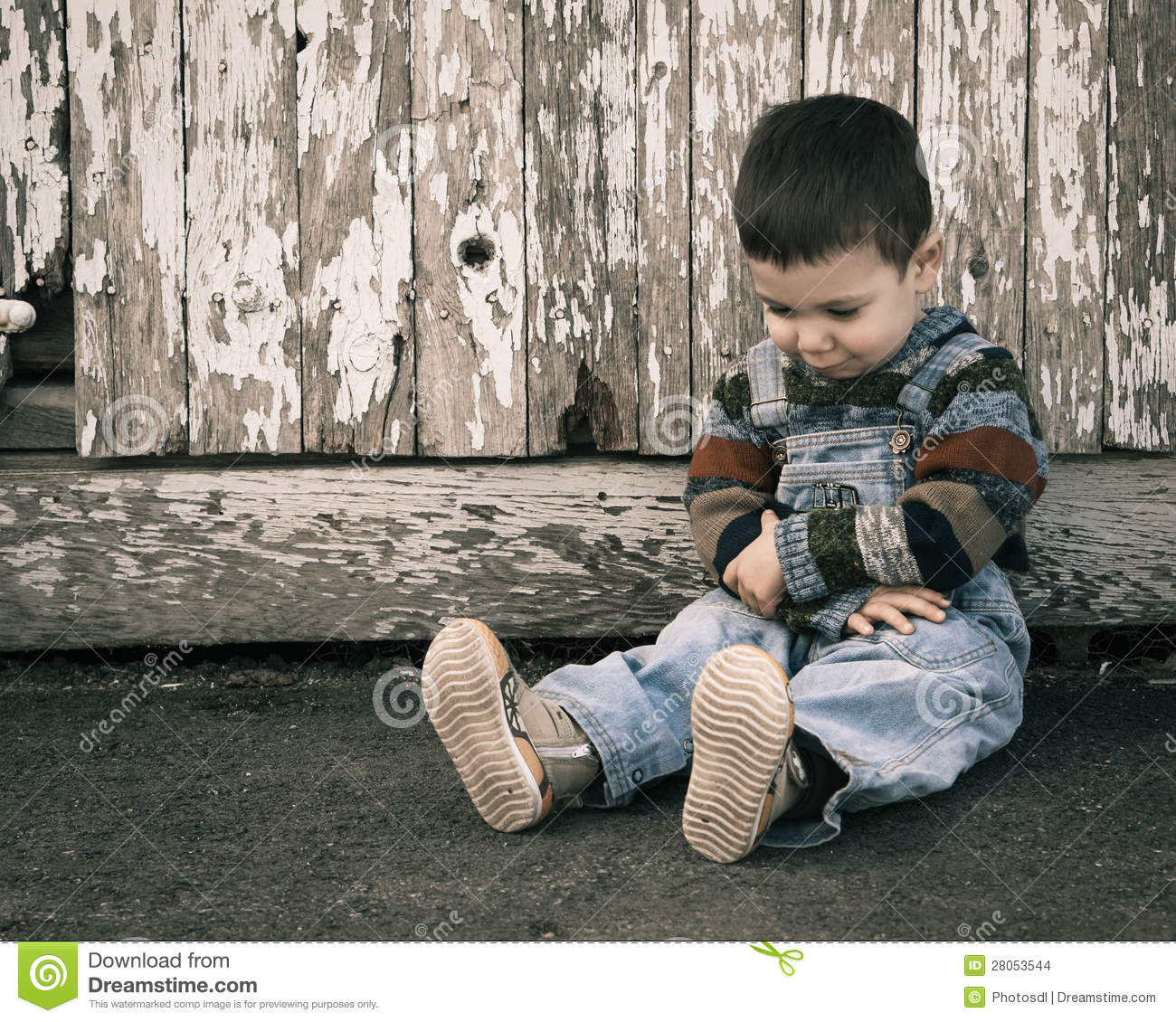 Sad lonely boy sitting near a wooden wall. Vintage color.