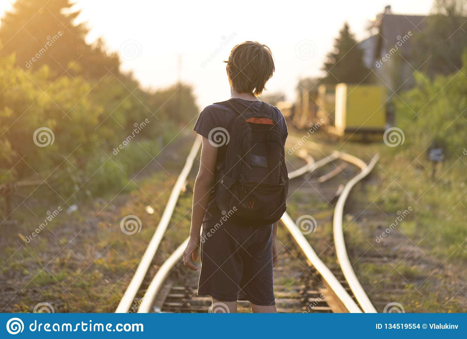 A lonely boy with a bag stand on the rails