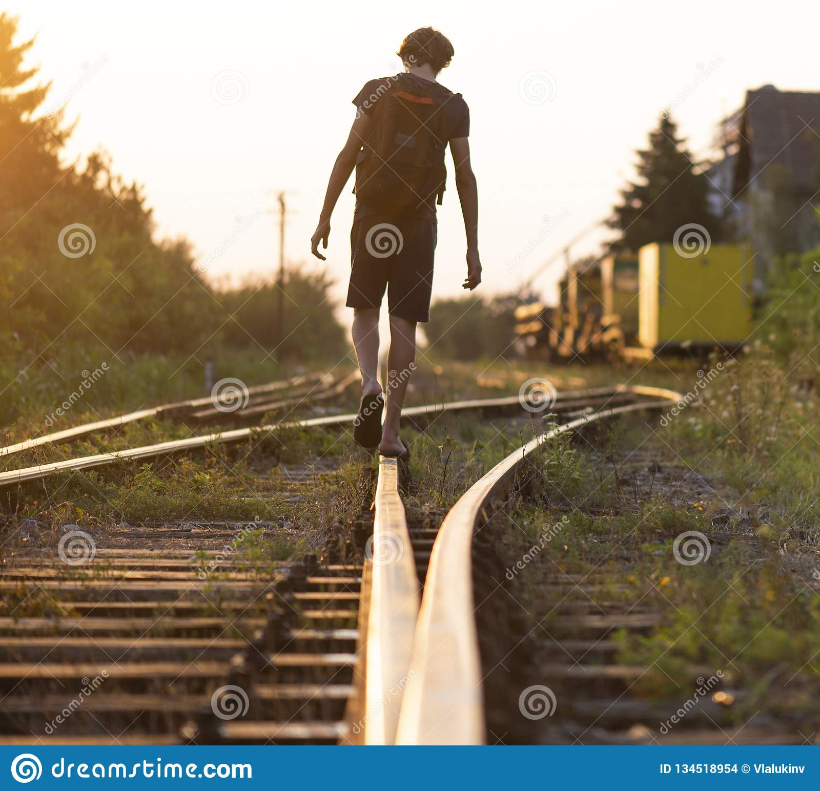 A lonely boy with a bag is walking on the rails