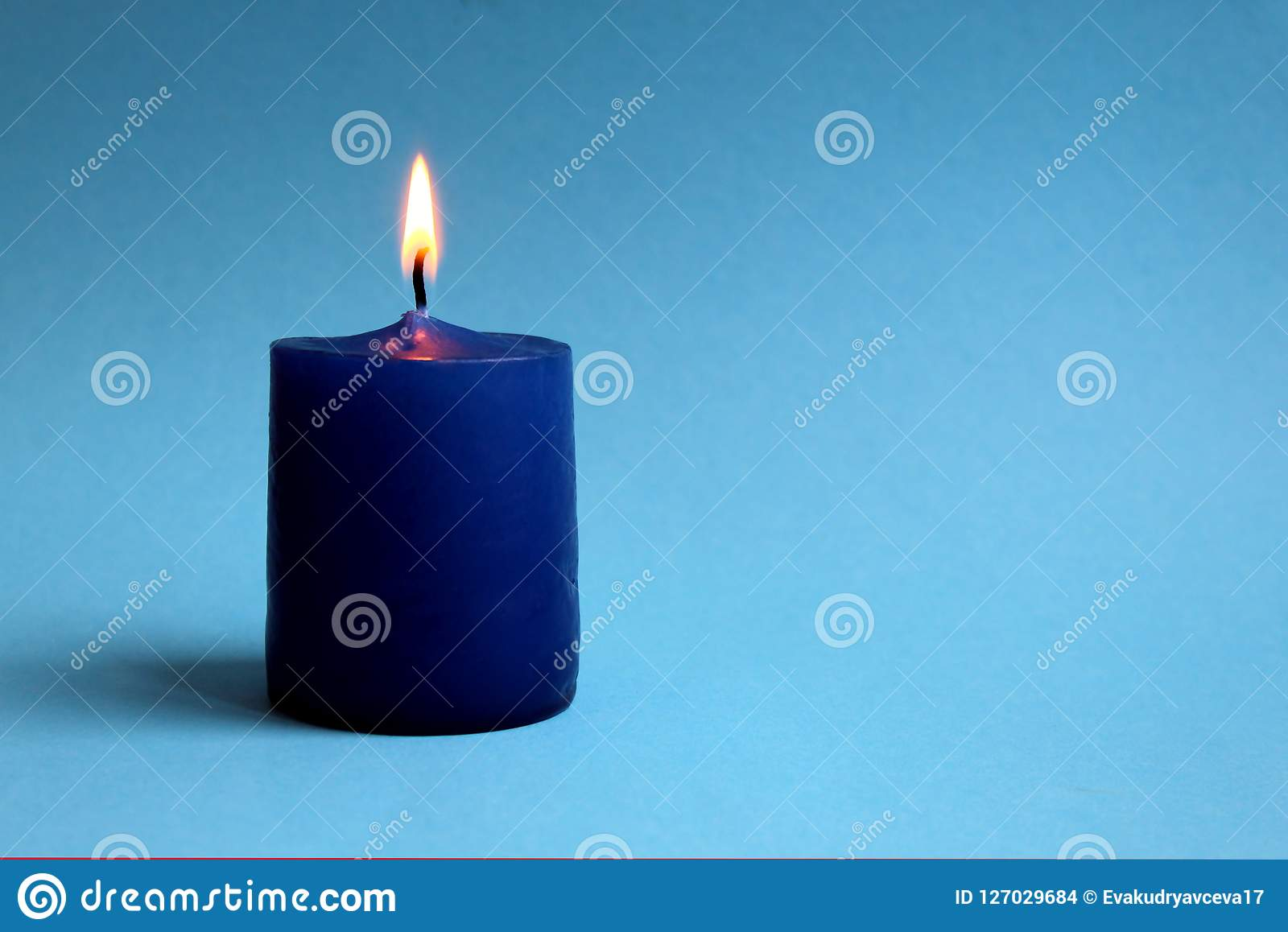 Lonely candle lit on a blue background