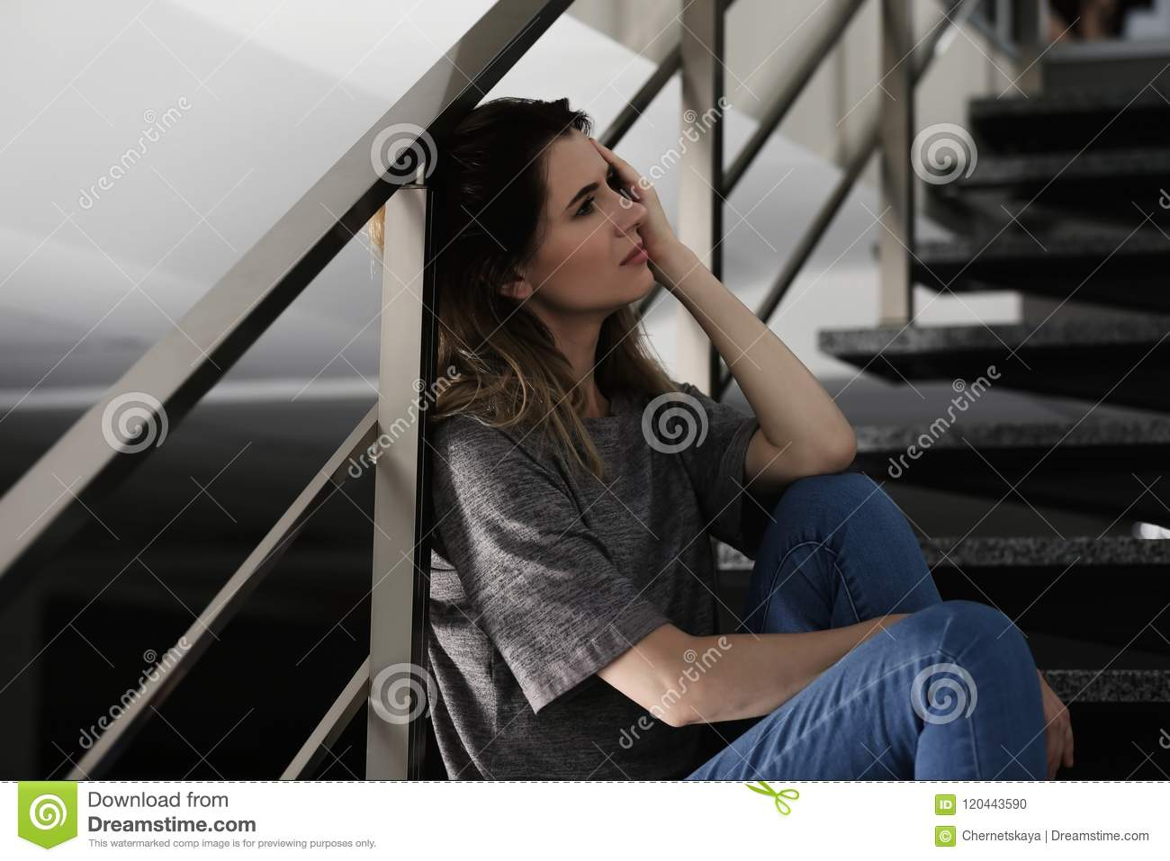 Lonely depressed woman sitting on stairs