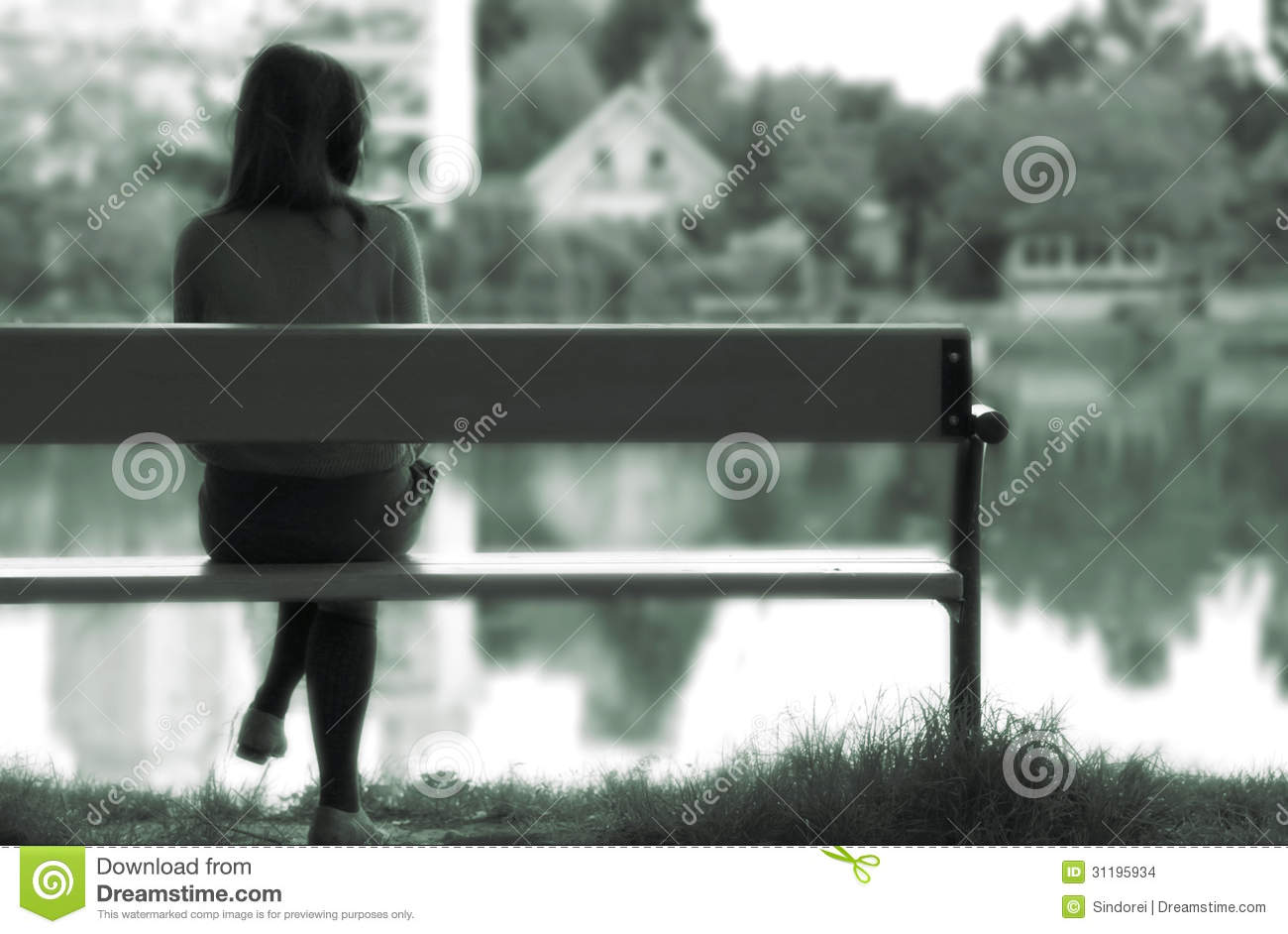Young lonely girl, lost in memories, is sitting on a bench next to a ...